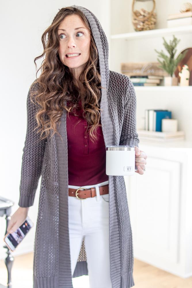 woman wearing hooded grey sweater holding white mug making a shocked face