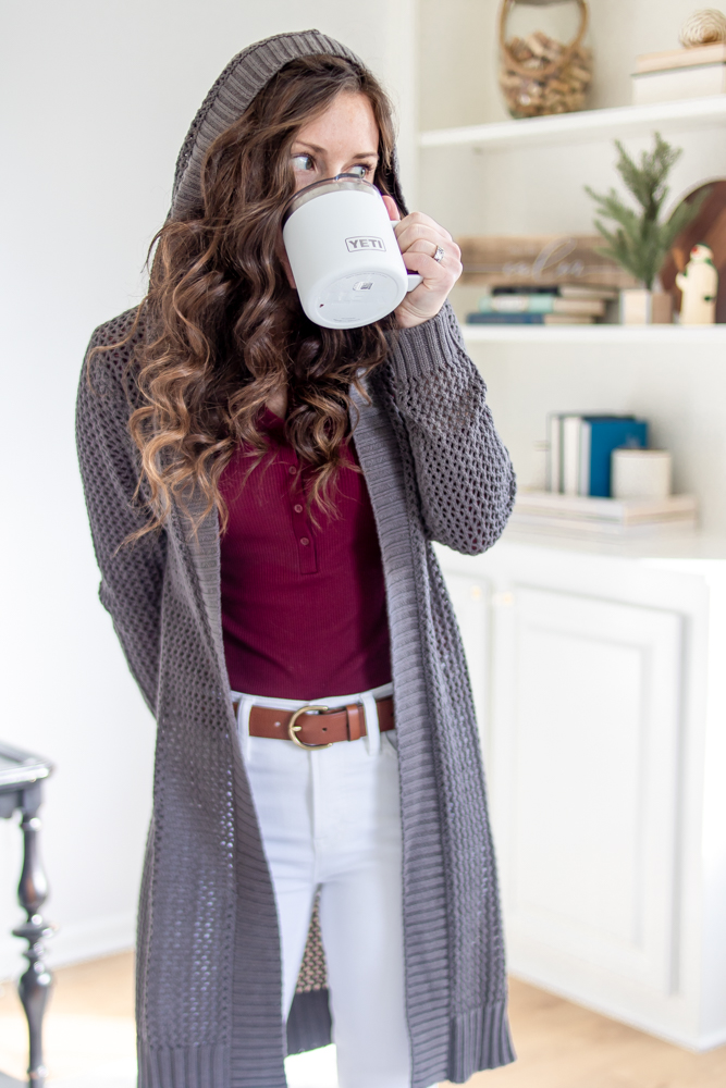 girl wearing hooded sweater and sipping coffee