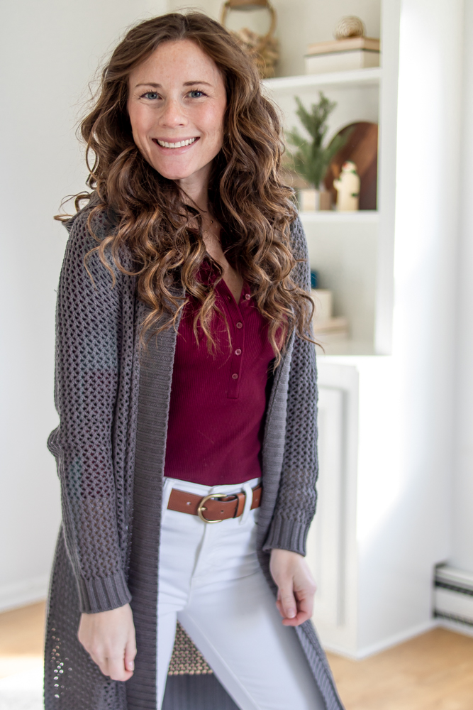 girl smiling wearing hooded grey sweater over a maroon shirt