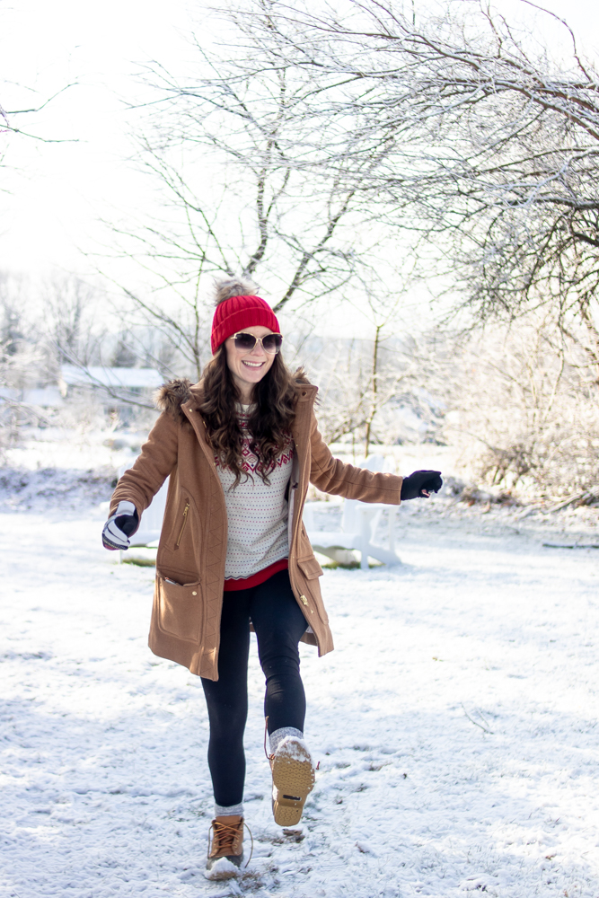 woman wearing tan coat red hat and snow boots kicking up snow outside