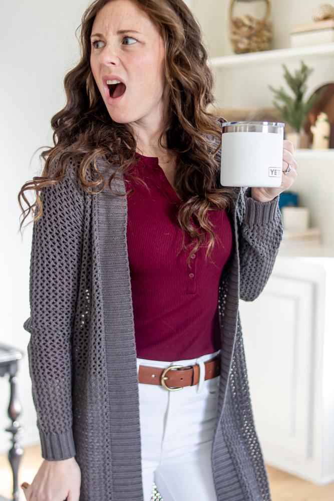 girl wearing maroon shirt grey sweater white pants with shocked face holding yeti mug