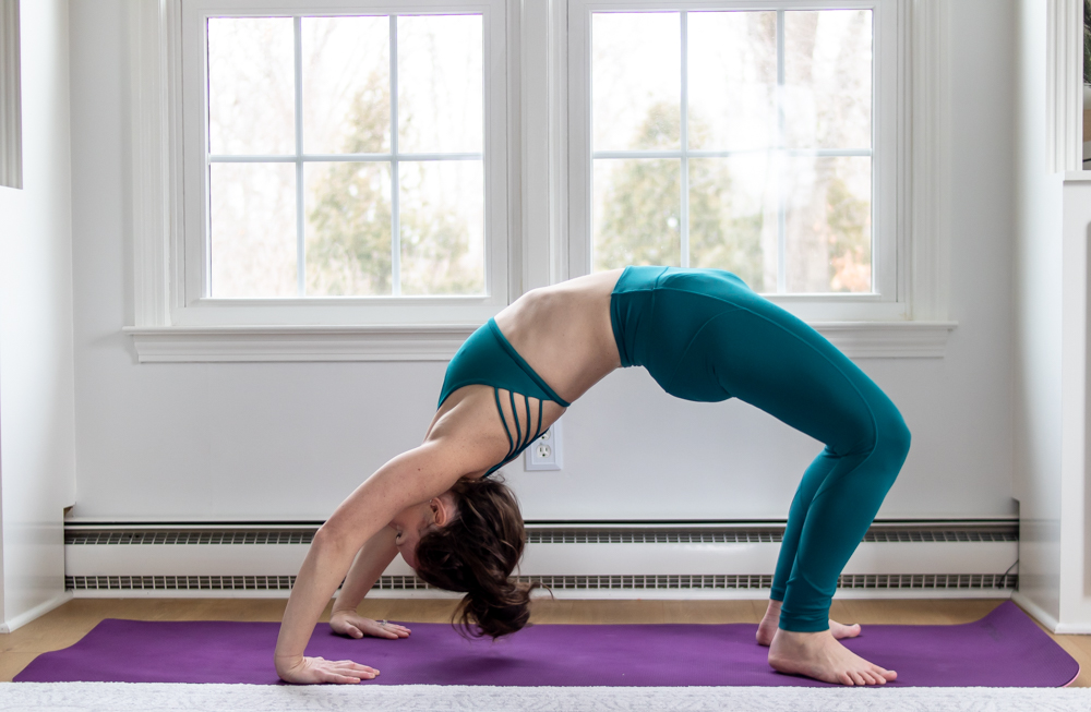 woman in green doing wheel pose for yoga