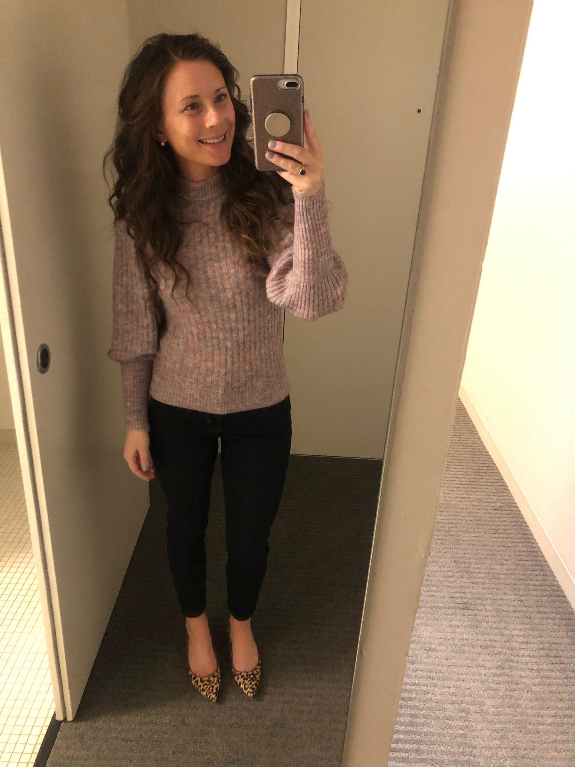 woman taking selfie in mirror wearing a purple sweater and dark jeans with leopard heels