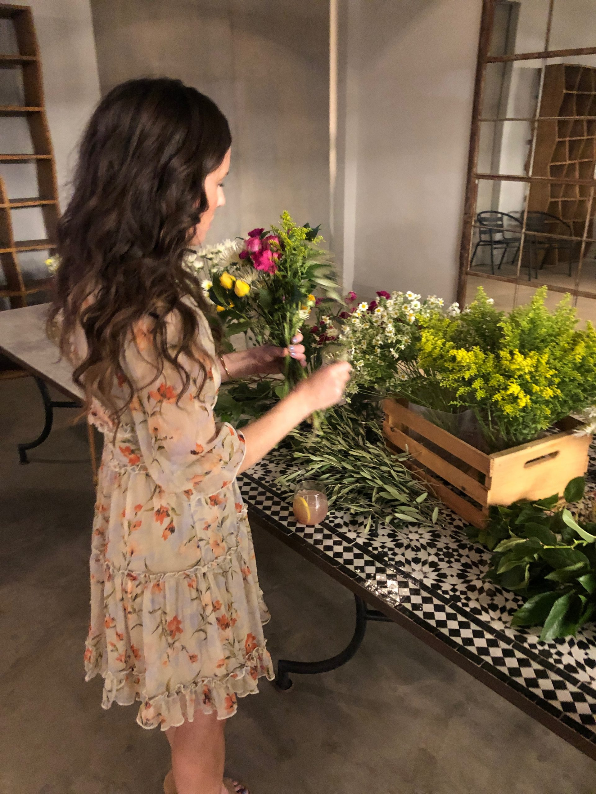 woman in tan floral dress making a bouquet