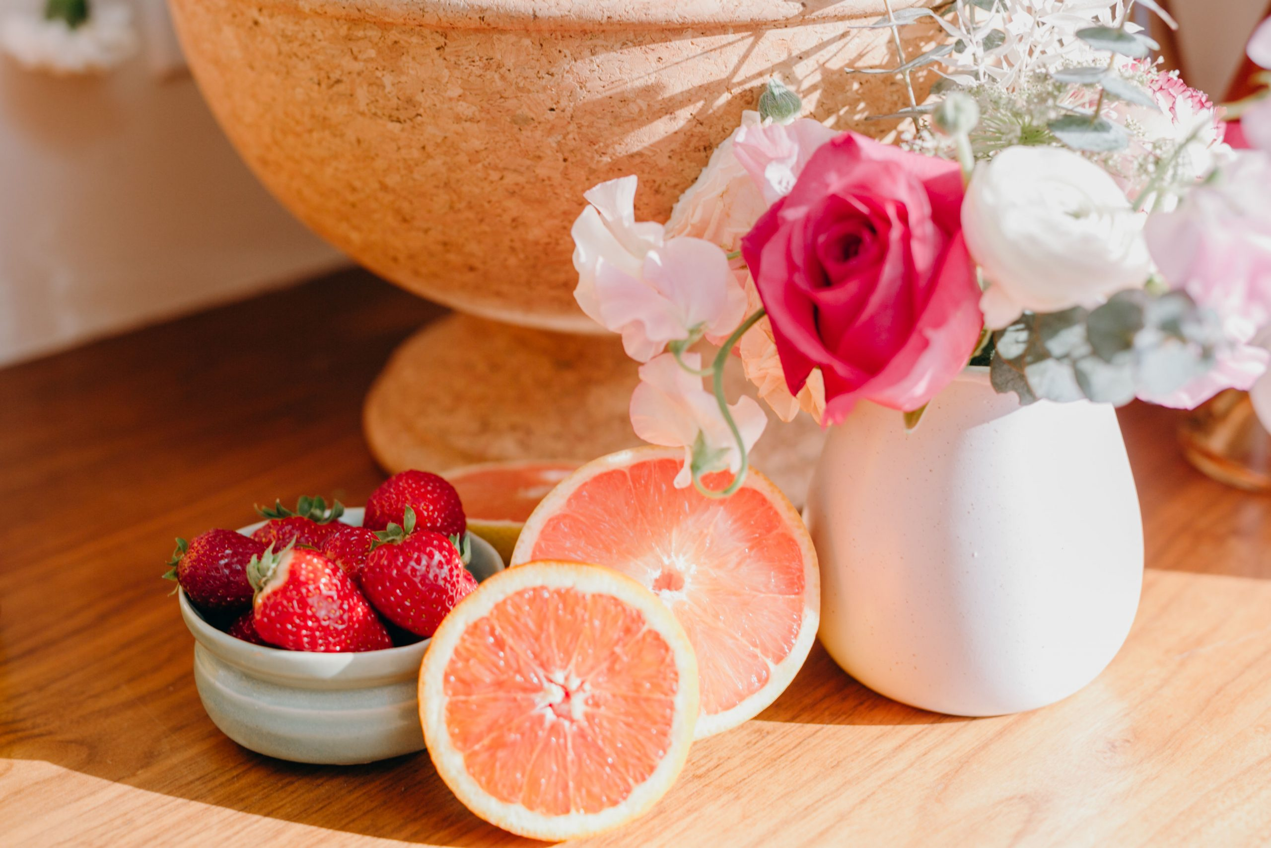 fresh grapefruit and strawberries with floral bouquet