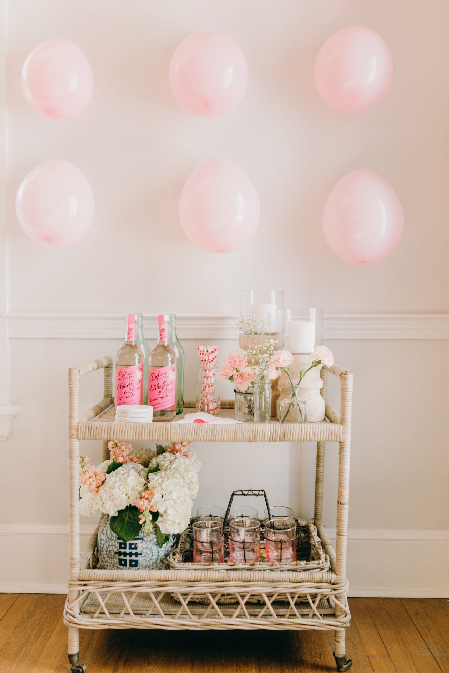 rattan bar cart decorated for valentine's theme pink balloon wall
