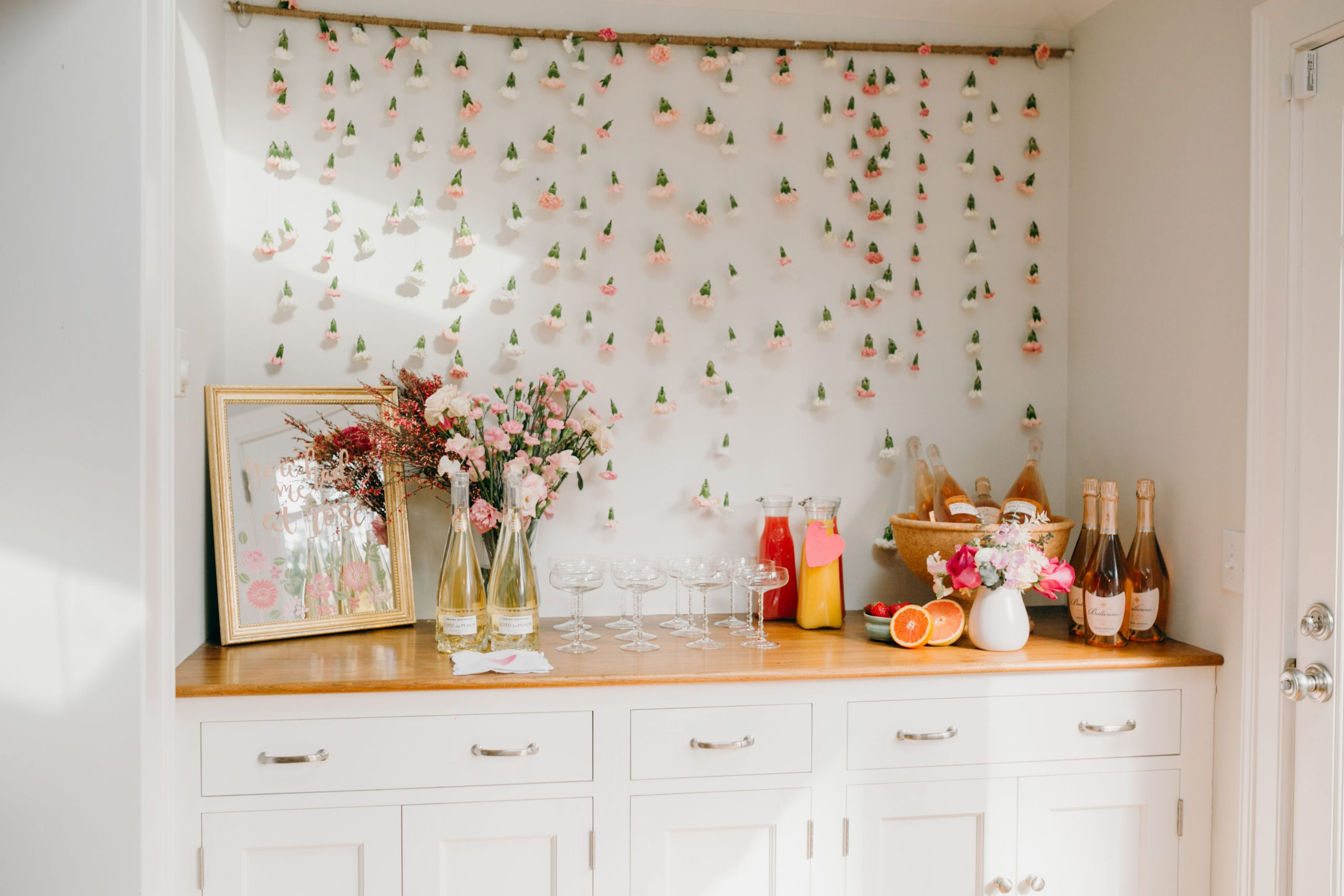 floral wall behind build in bar at home stocked for galentine's day brunch