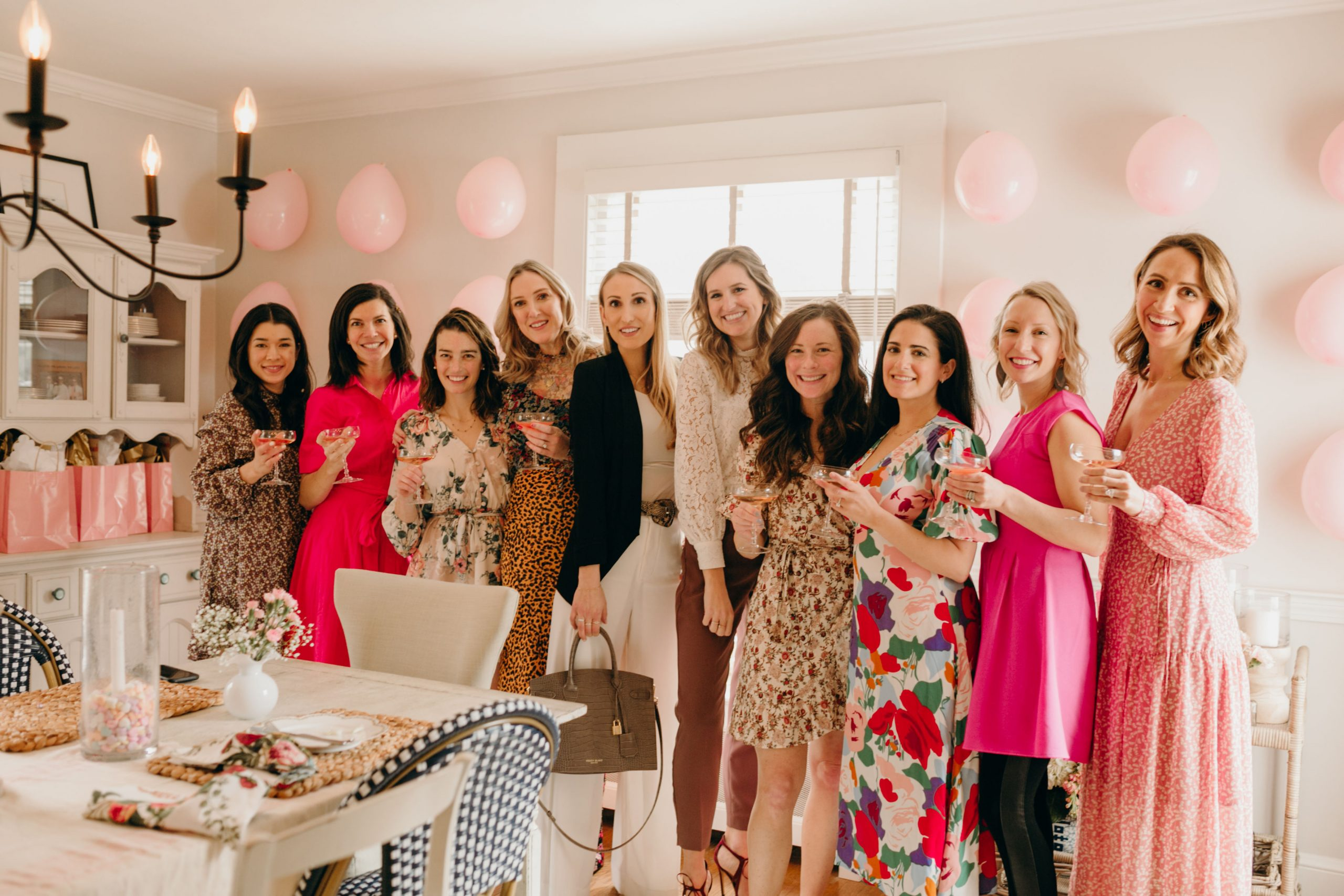 women in floral dresses holding rosè in champagne glasses