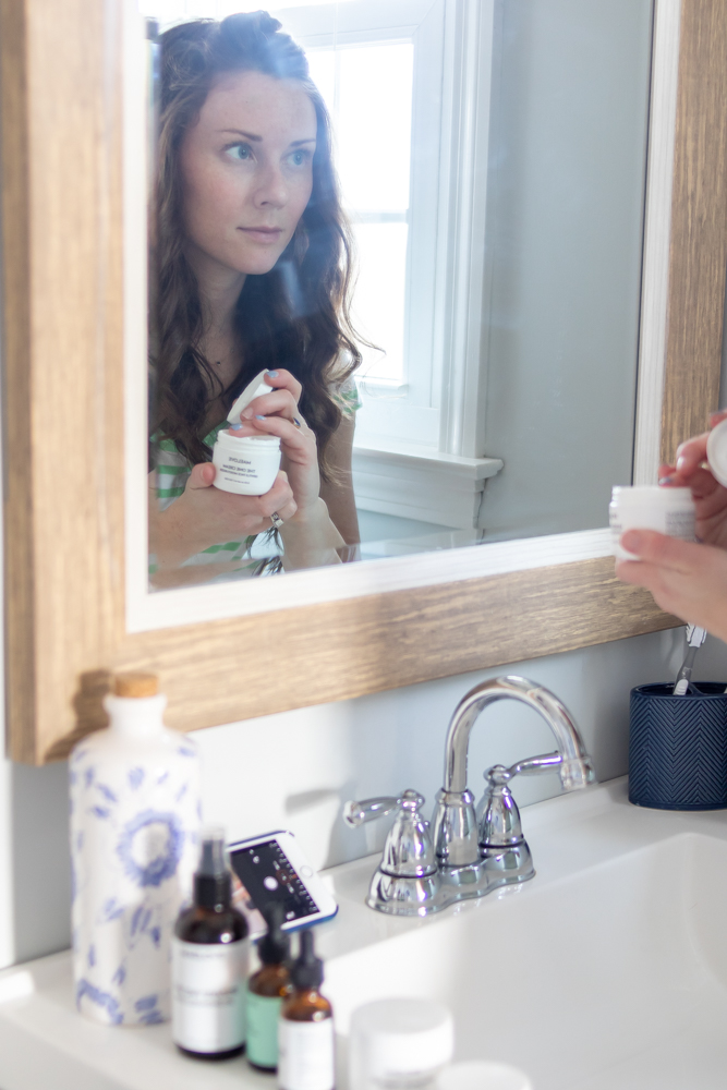 Woman sticking her finger in a tub of skin moisturizer