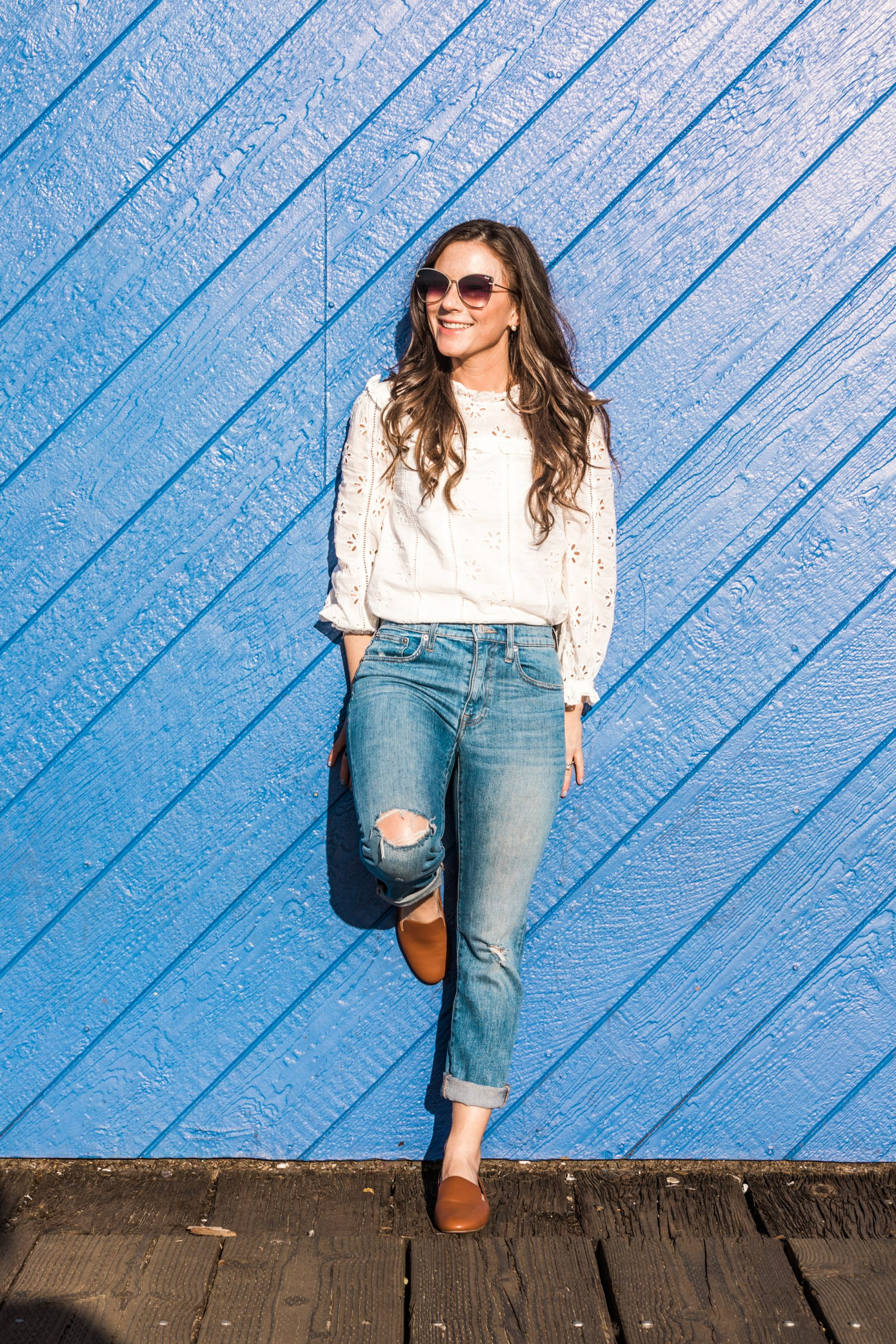 Woman standing in front of blue wall smiling wearing an eyelet shirt jeans and brown leather shoes