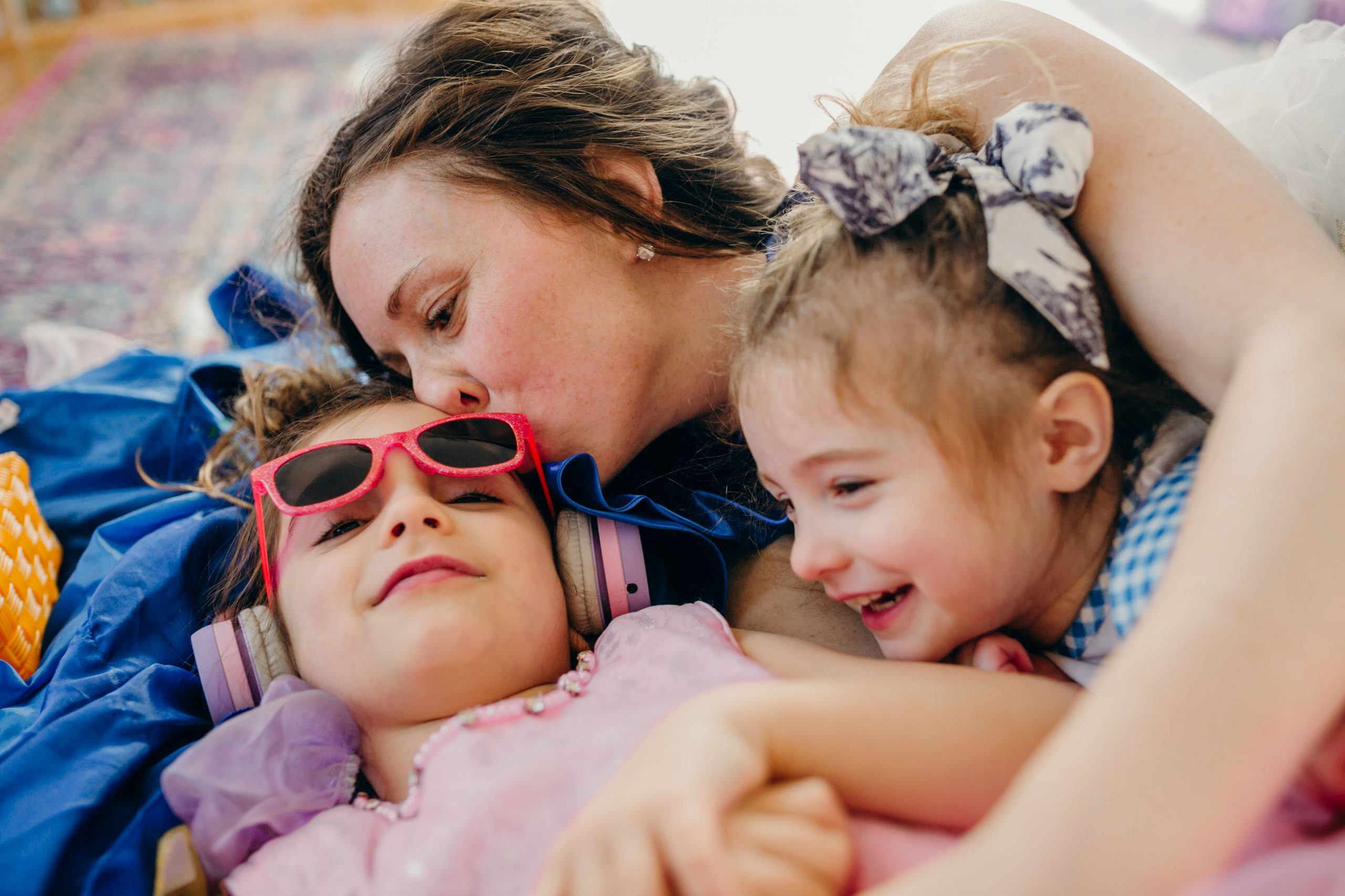 super hero mom smooching little girls in dress up clothes