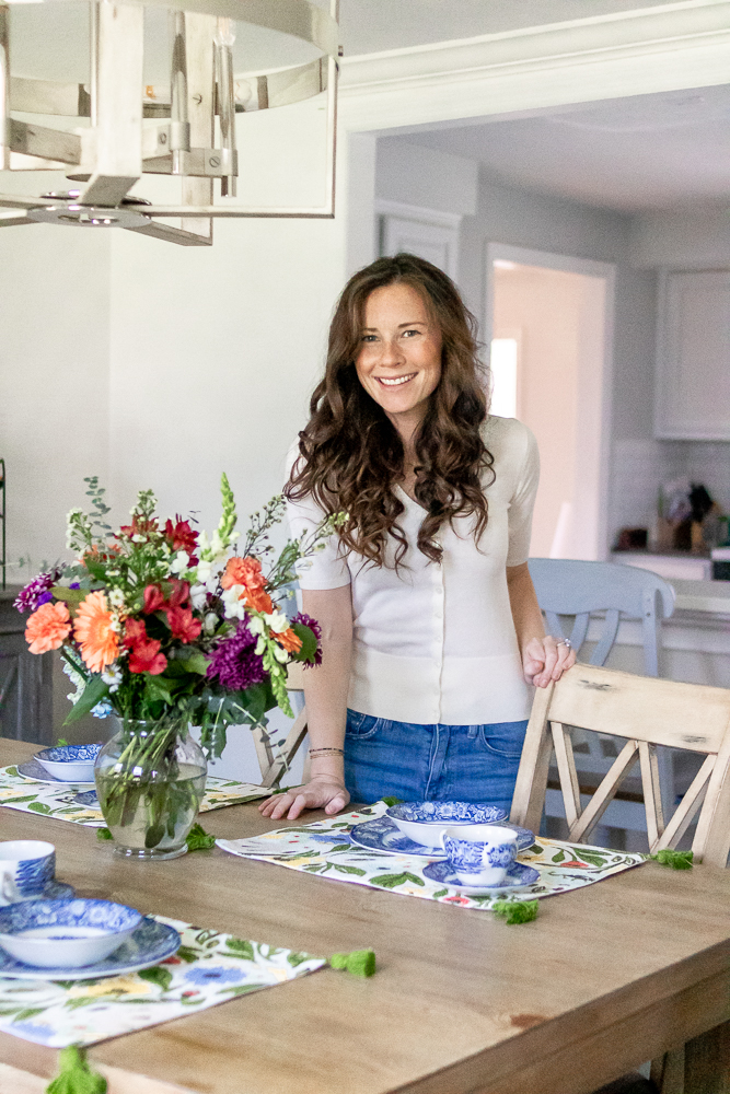 woman placing flowers on dining room table