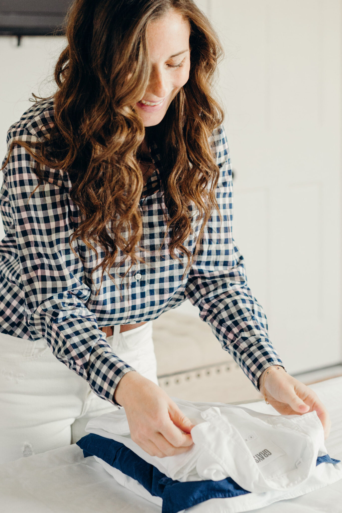 woman folding button down shirts on bed