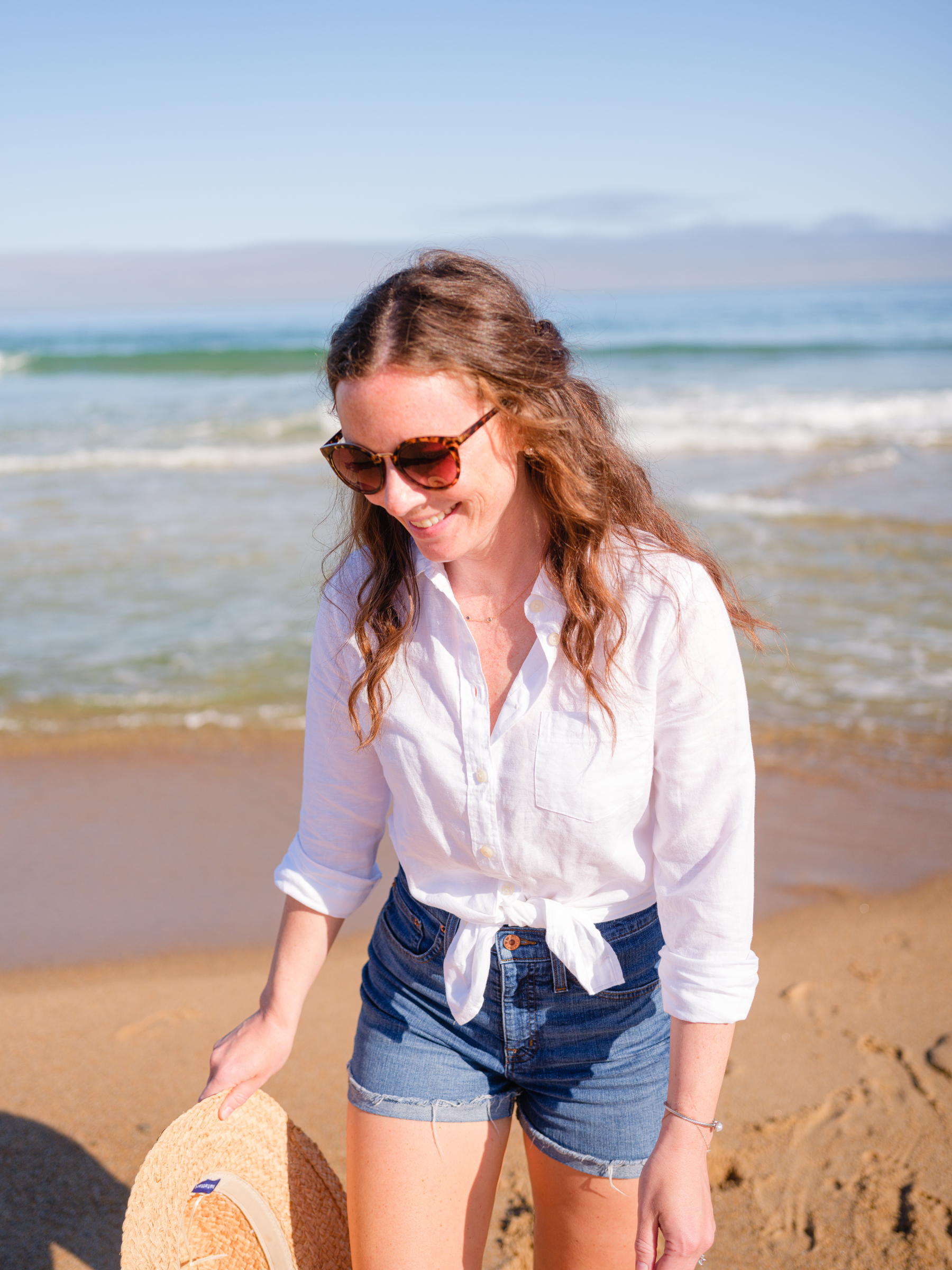 woman at beach with summer hat and white linen button up