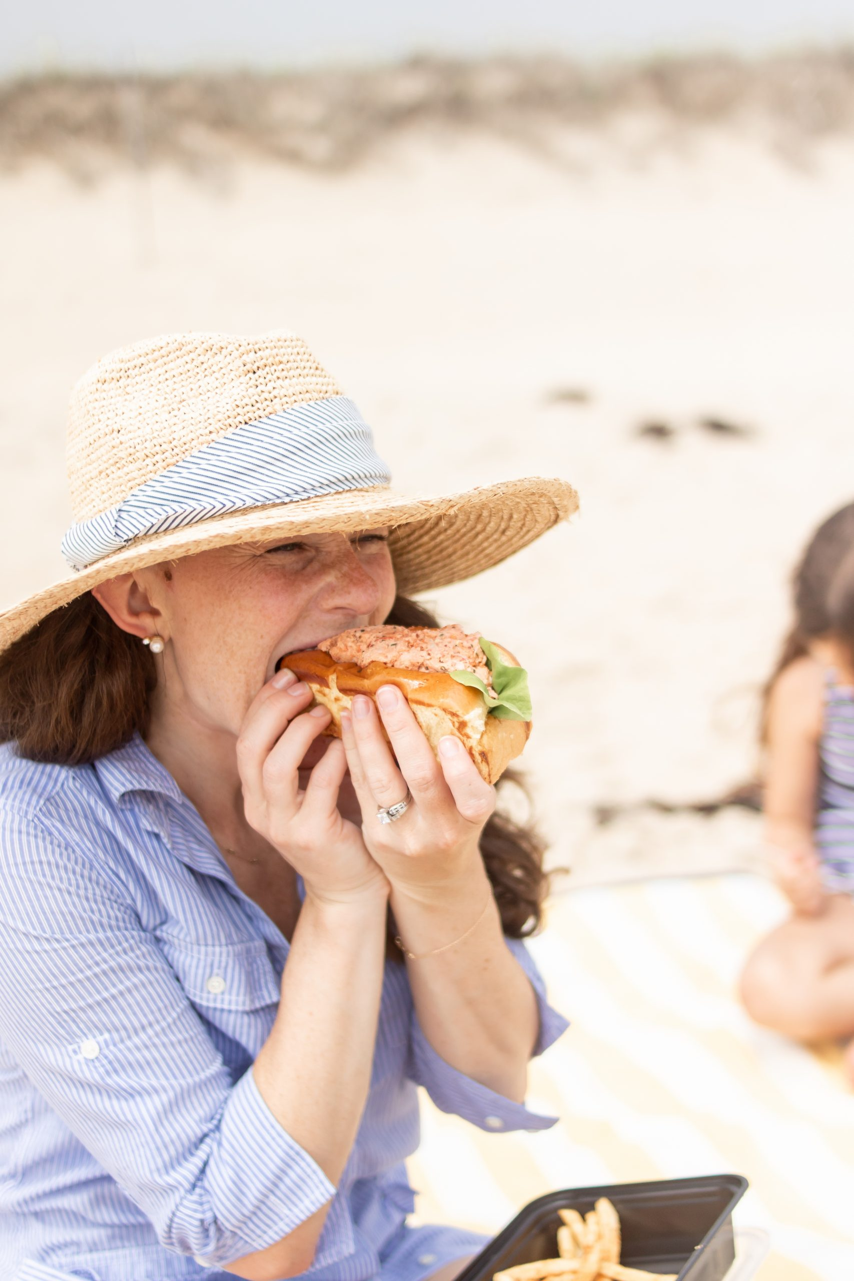 Woman eating lobster roll at Picnic Lunch on the beach