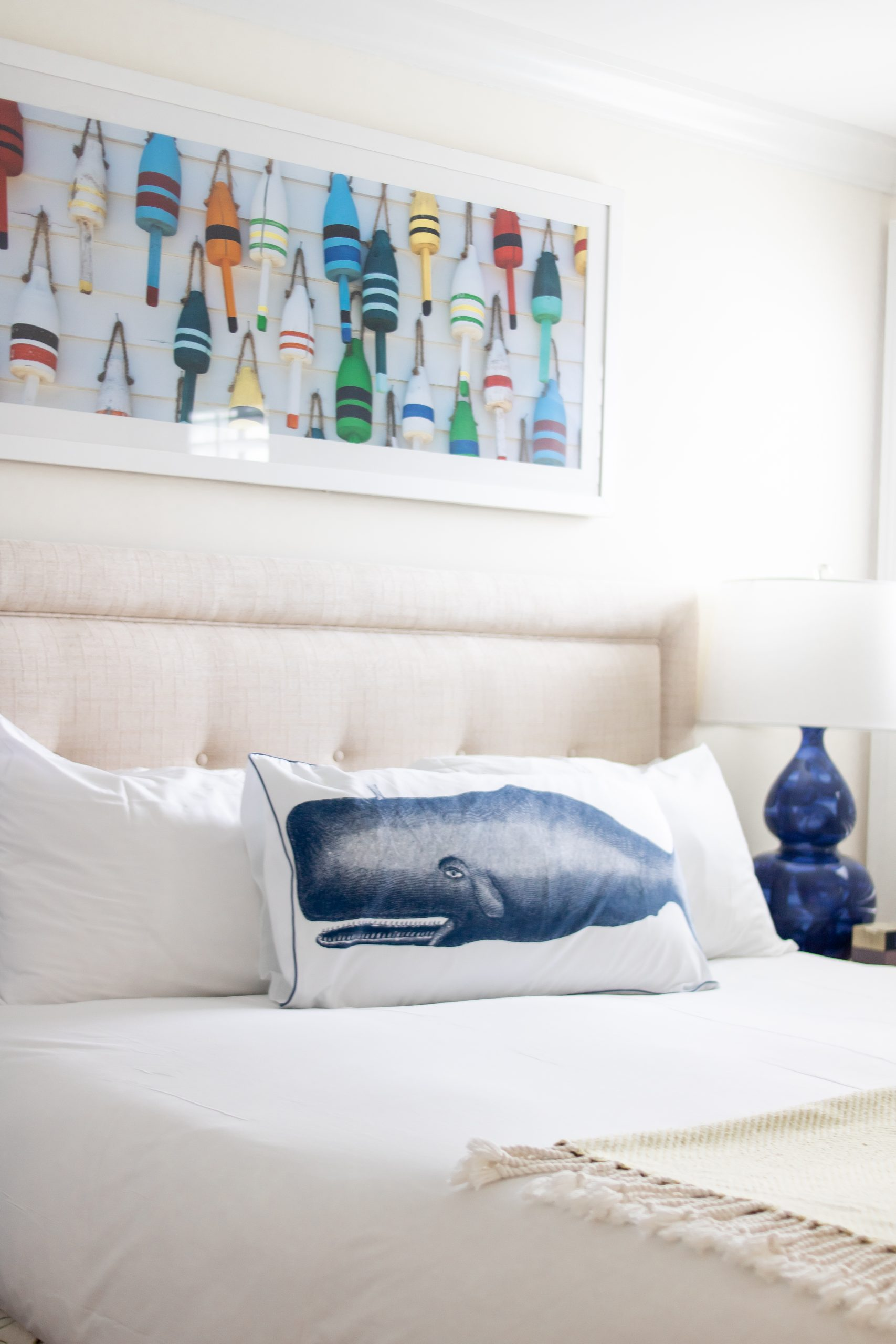 buoy painting above bed with whale pillow at Nantucket Hotel