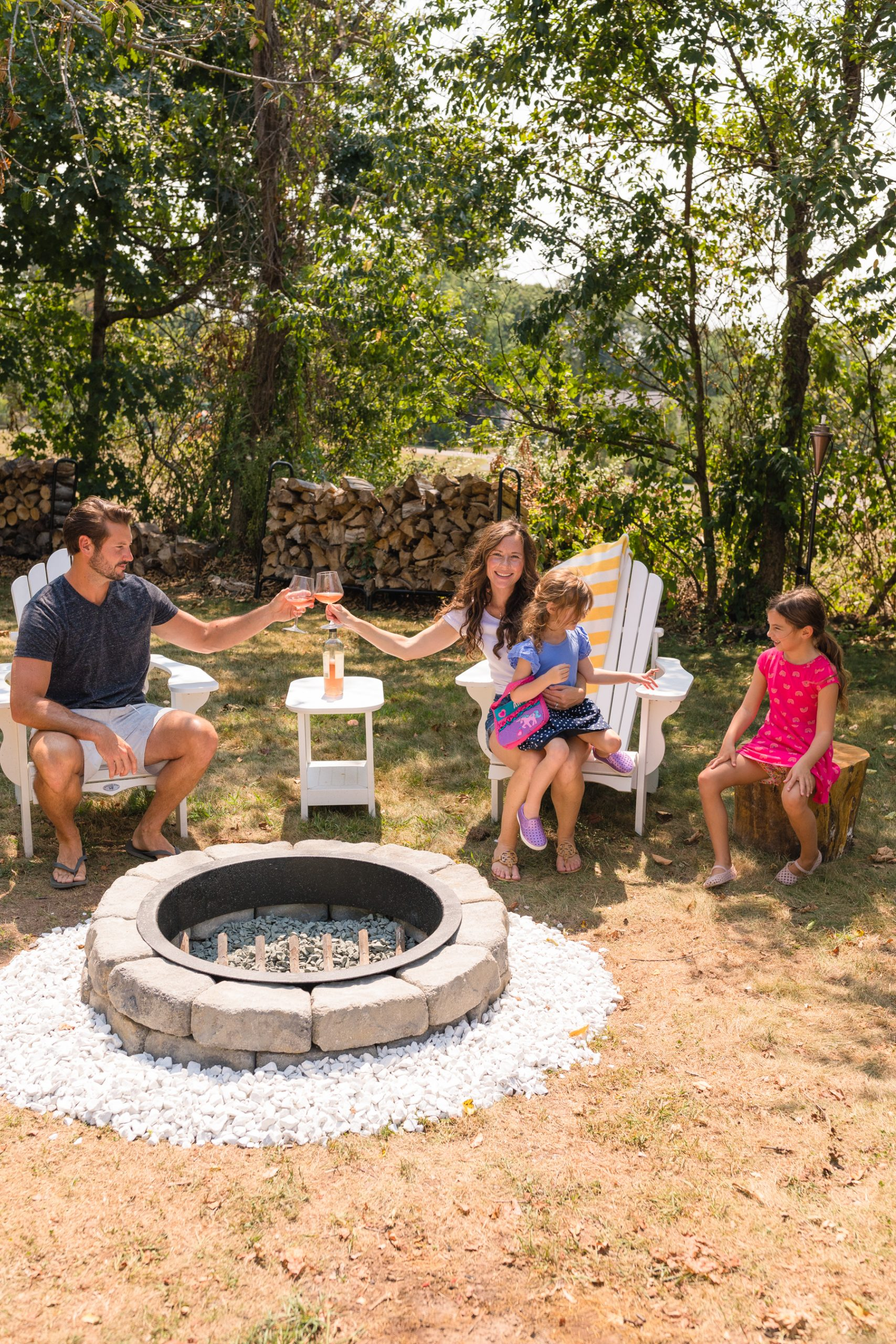 Family sitting in Adirondack chairs around stone fire pit in late August 2020