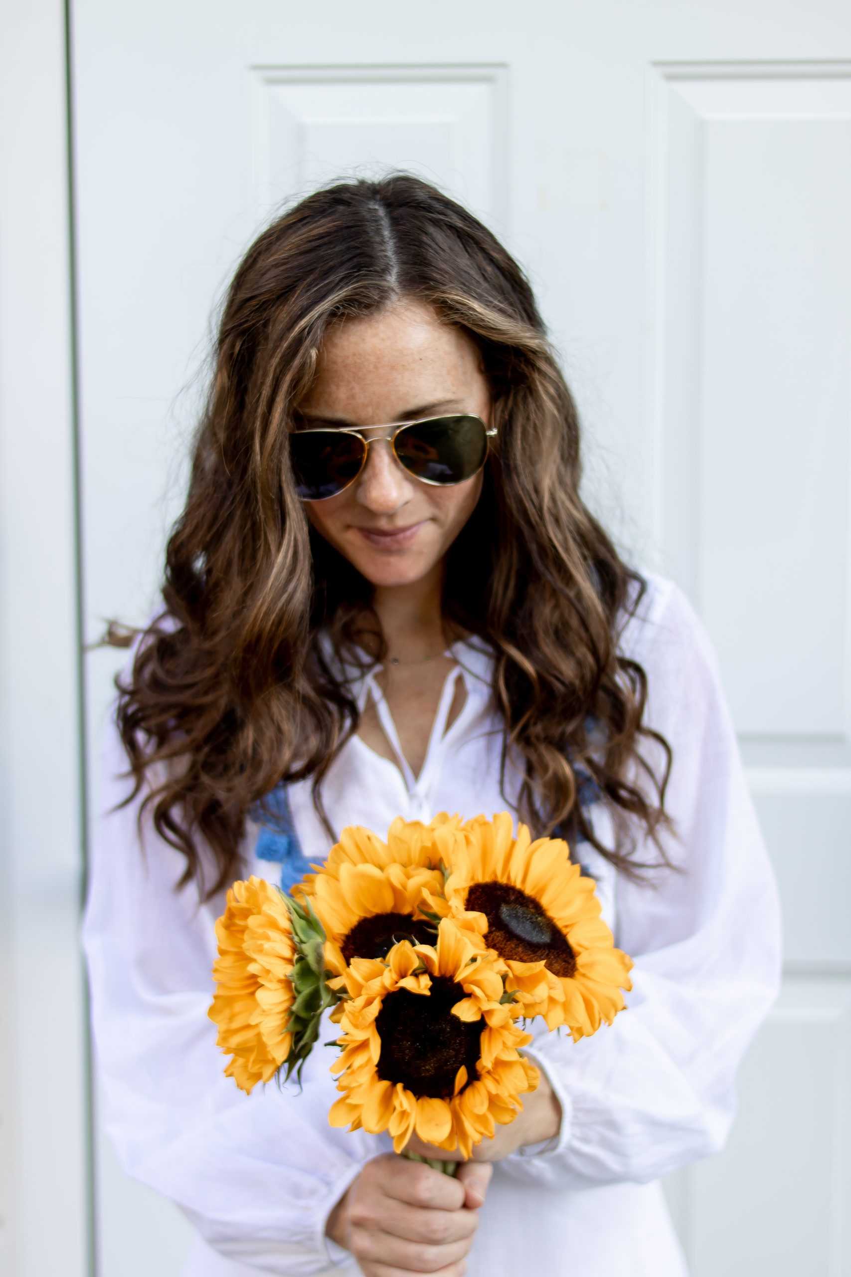 Girl holding sunflowers wearing Sail to Sable Tunic