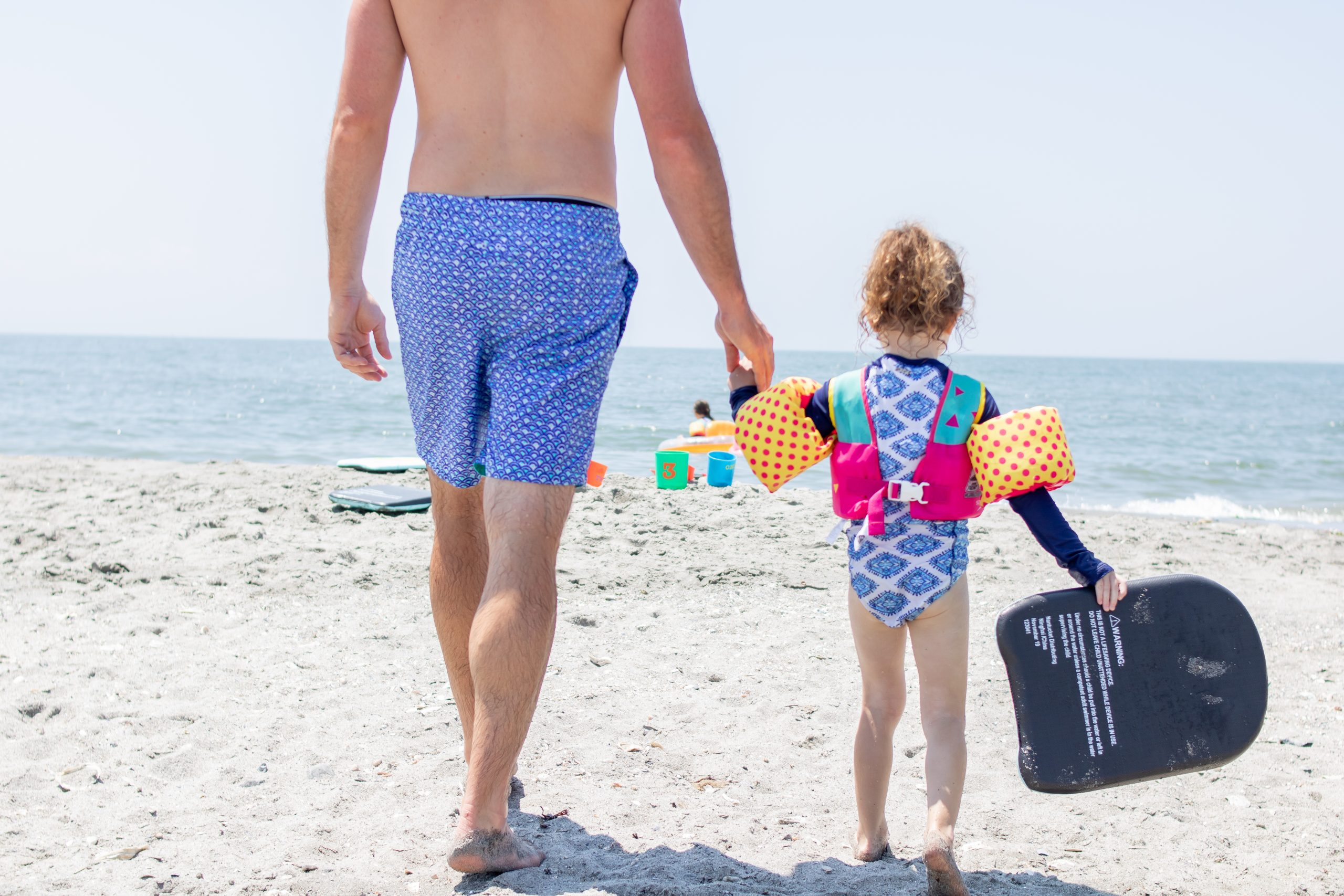 Dad and Daughter walking on the beach in July in matching swimsuits