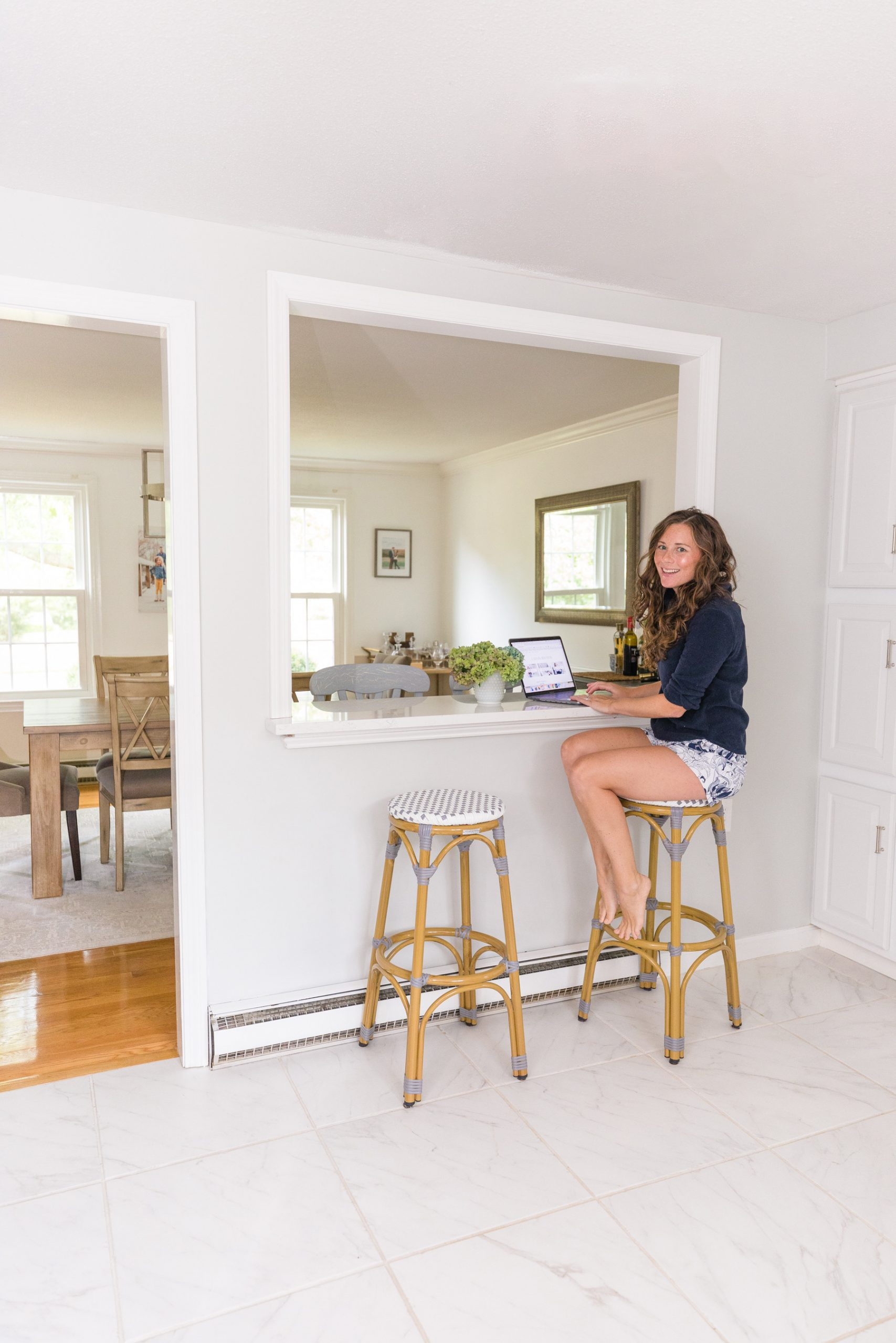 Woman sitting at Breakfast Bar with white quartz countertop in kitchen with serena lily riviera dupe stools
