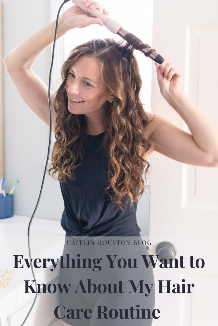 woman wearing all black using a wand to wave her hair