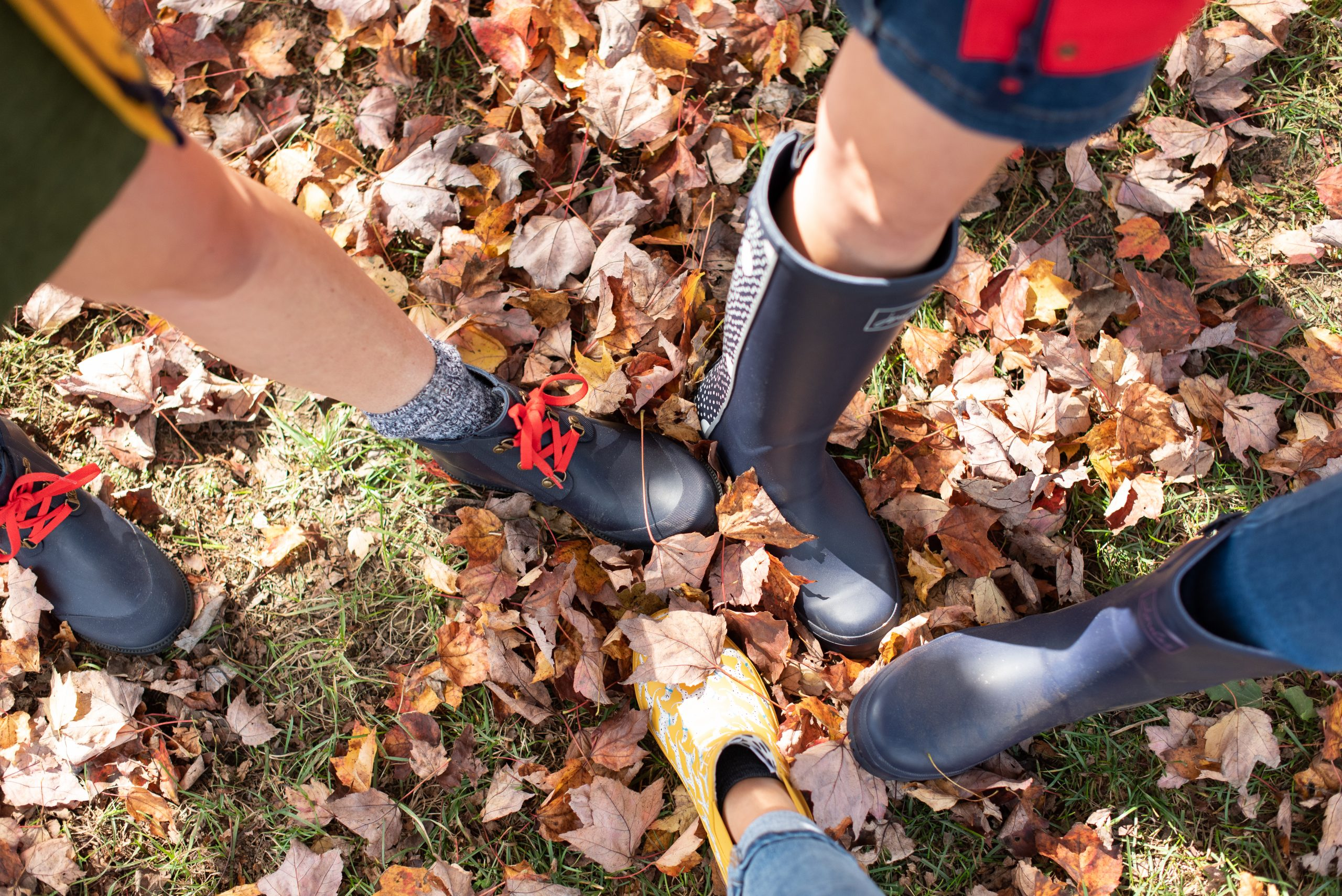 girls wearing Joules rain boots putting feet together on fall leaves