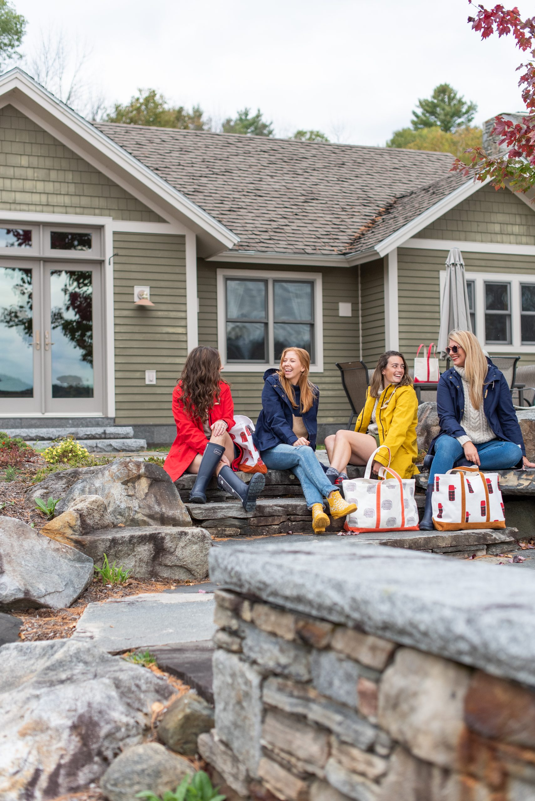girls wearing Joules rain coats sitting on steps with their bags in vermont at lake house during the fall