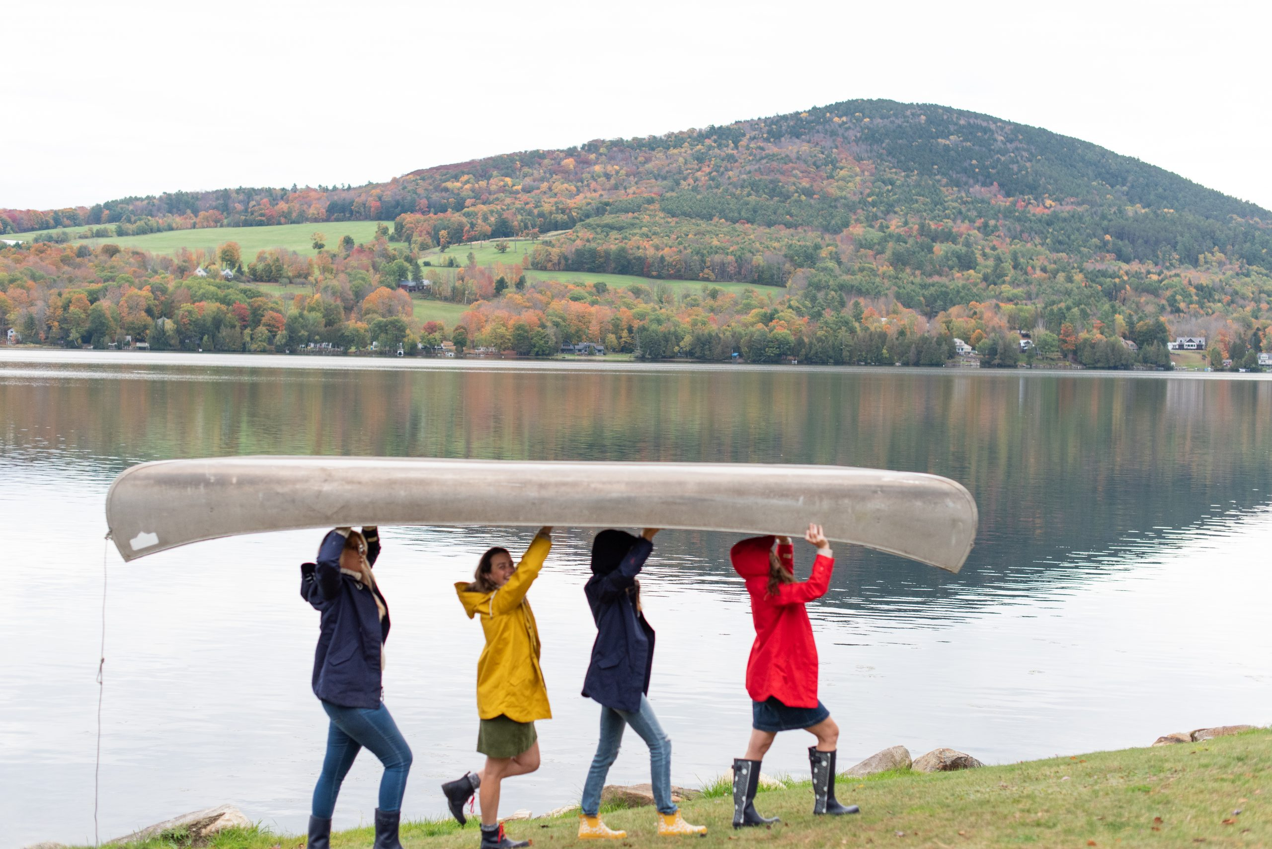 Girls carrying canoe above head in front of Harvey Lake Vermont