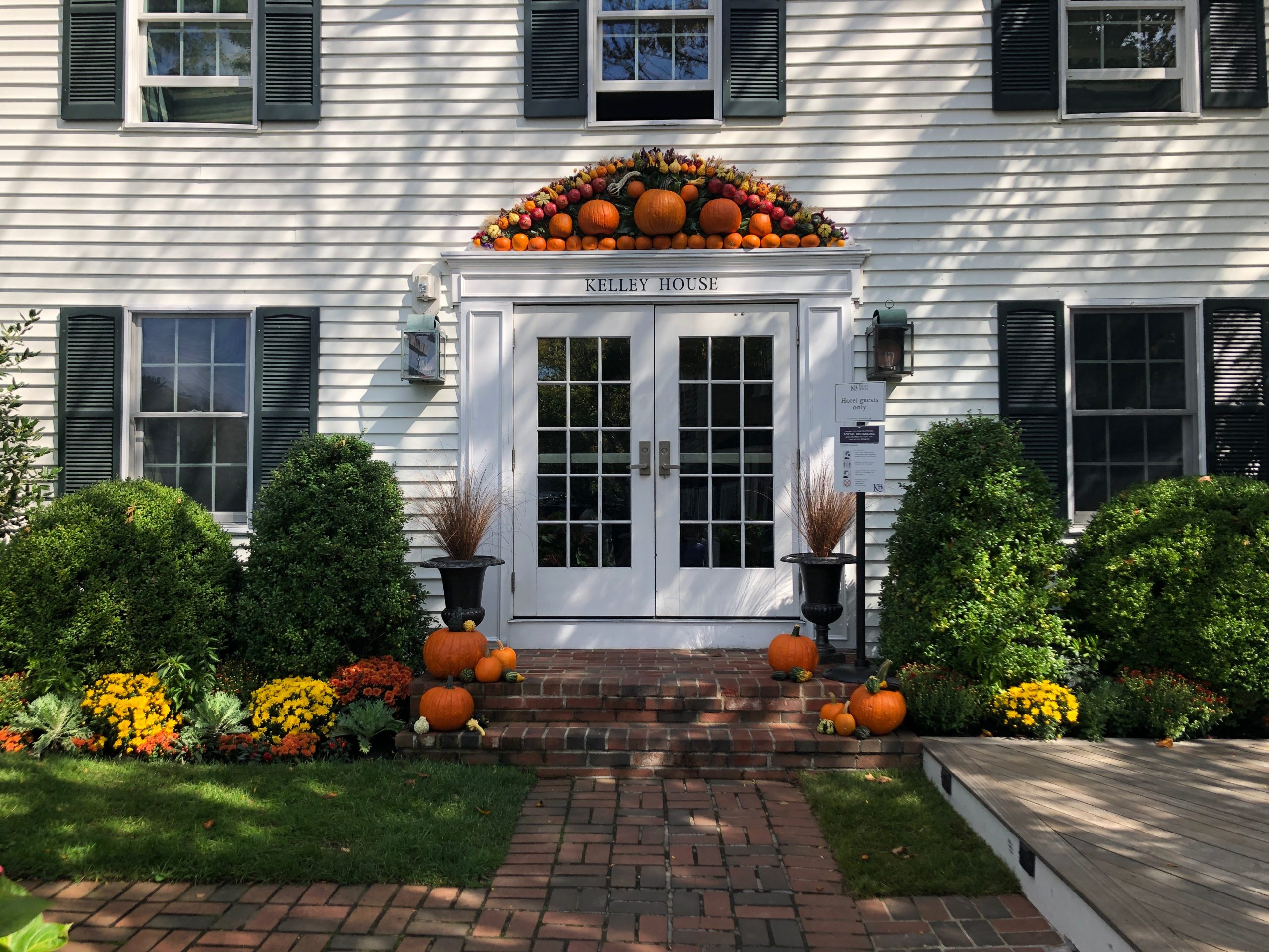 White Colonial Home with Pumpkin Decor Above Door