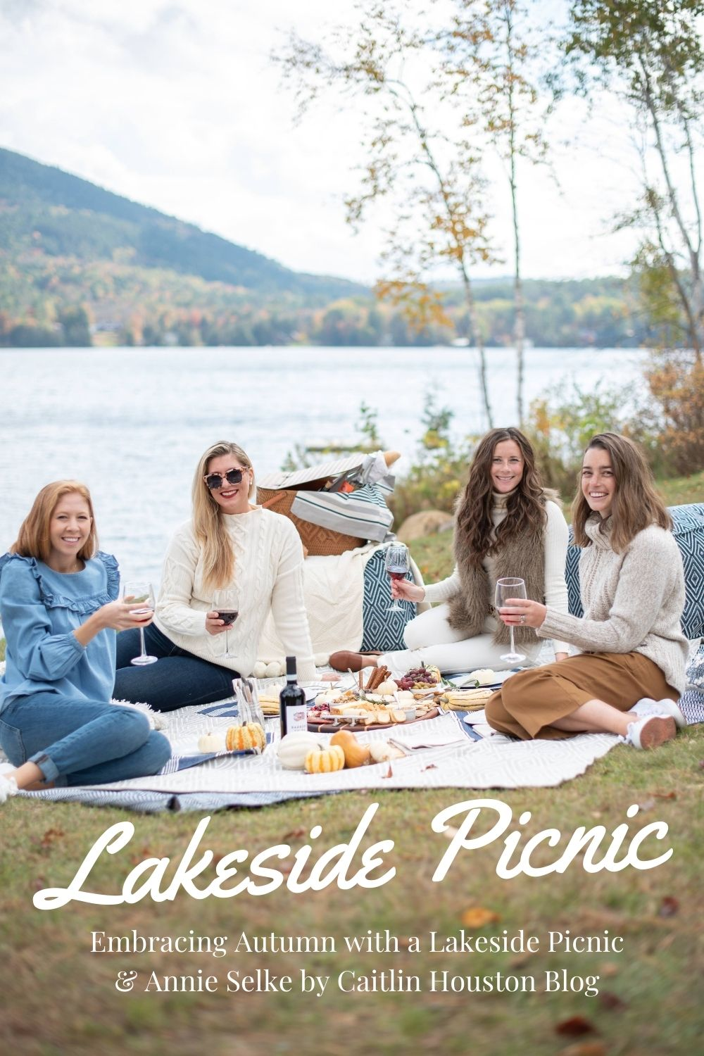 girls with wine glasses sitting on outdoor rugs at a lakeside picnic in Vermont
