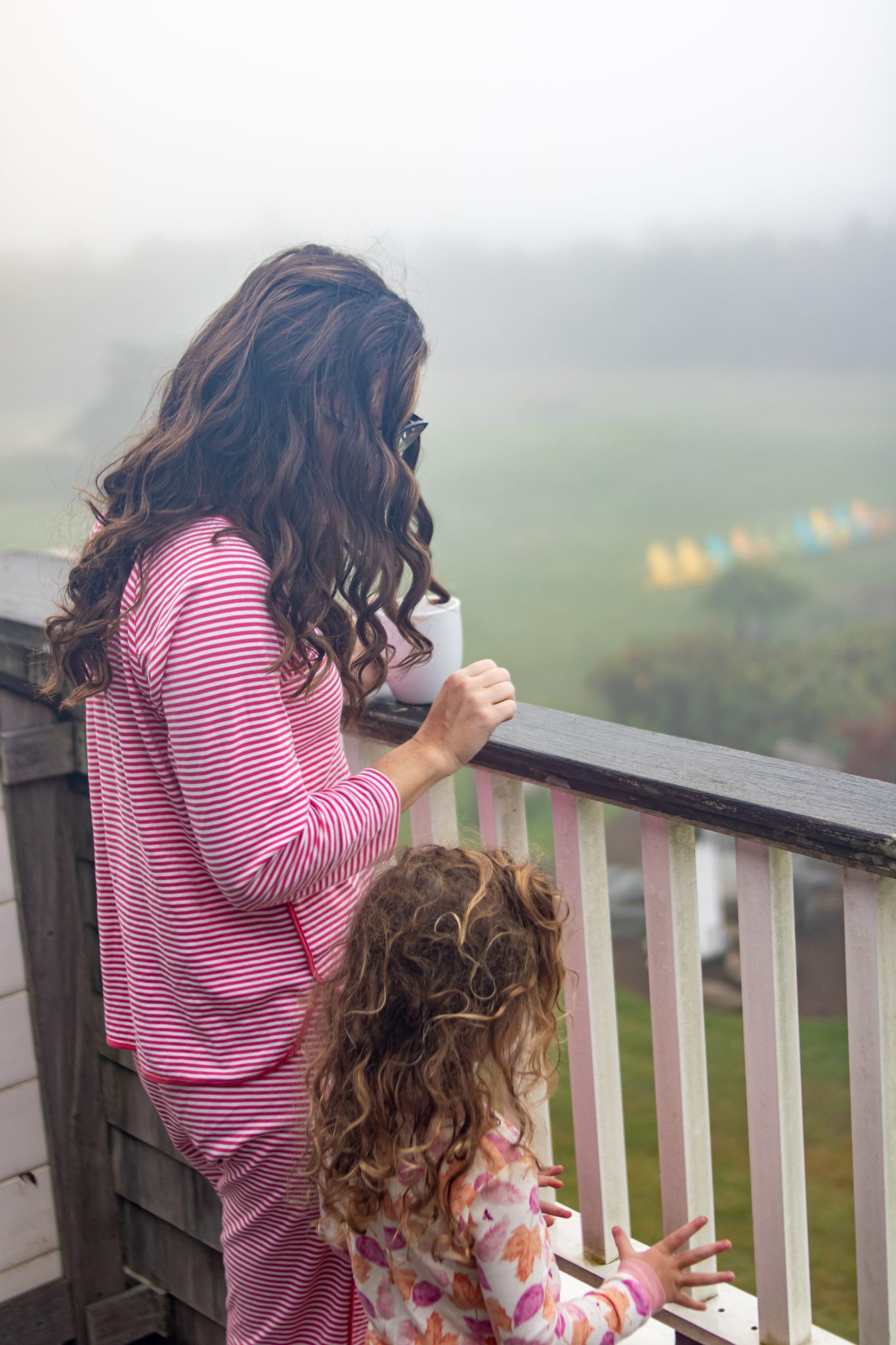 Mom in Lake Pajamas and Curly Haired Girl in Burts Bees Baby Pajamas on Balcony at the Winnetu on Foggy Day in September