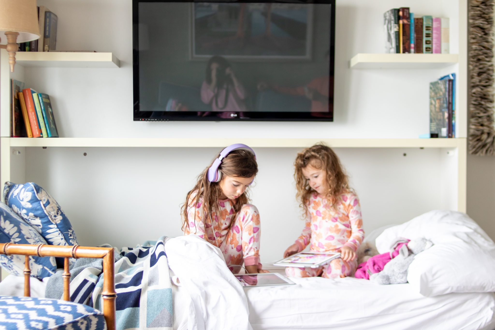 Little girls wearing fall pajamas sitting on the drop down twin bed in the West Chop suite