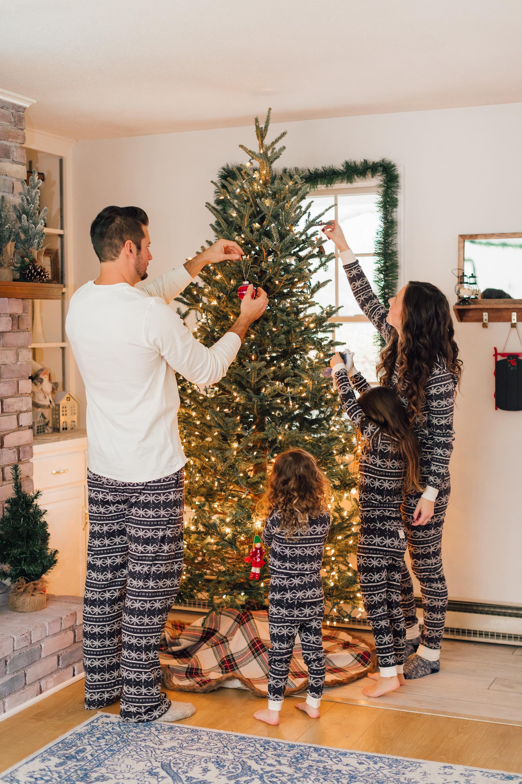 Family decorating Christmas tree in Christmas pajamas