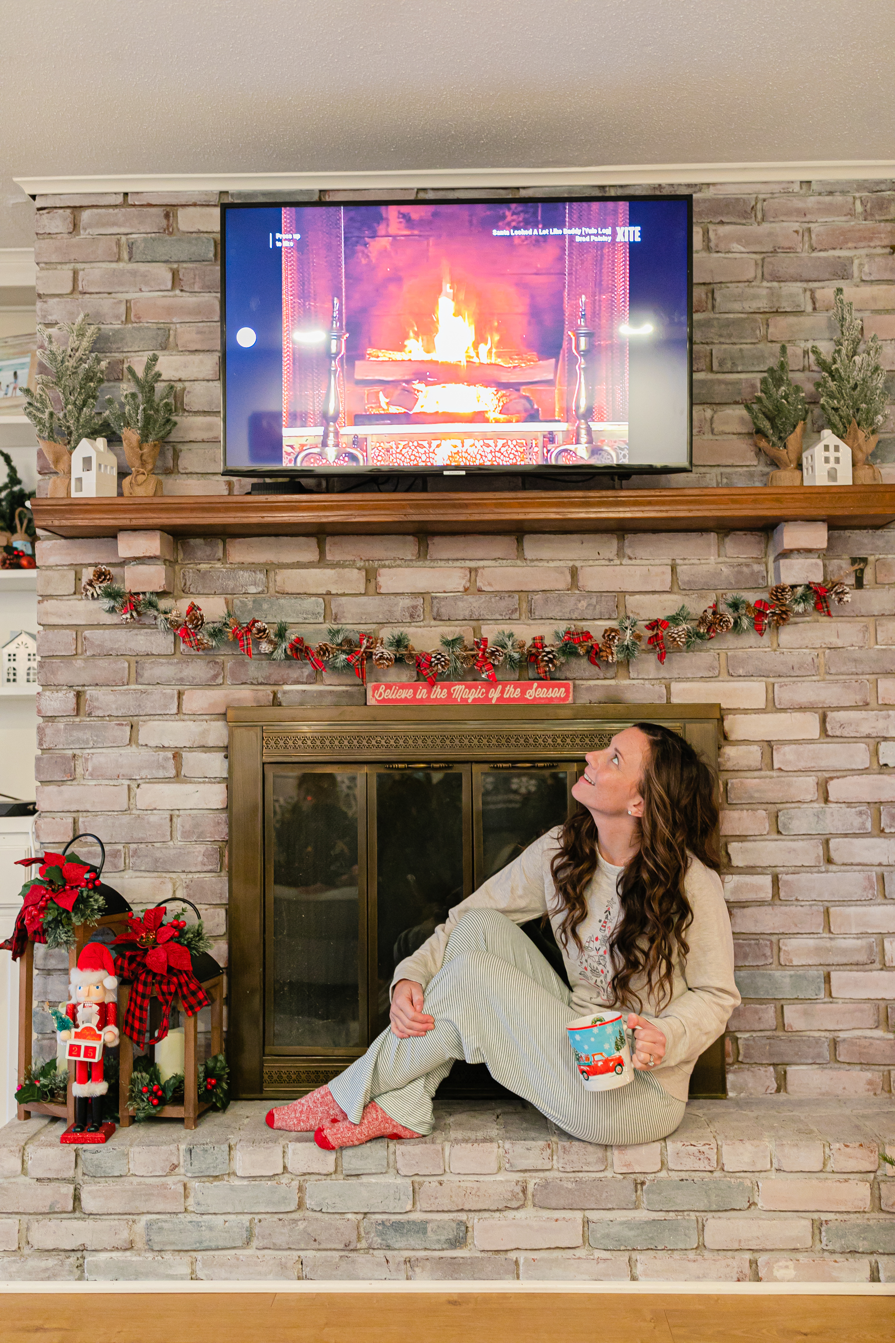 woman looking at yule log on tv for xmas with xfinity