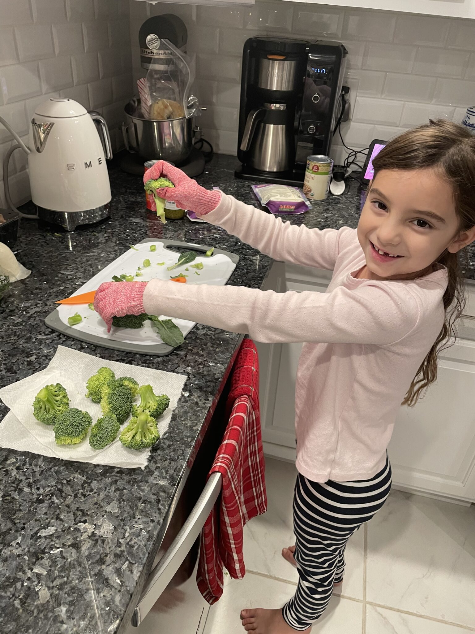 little girl using knife to help in the kitchen
