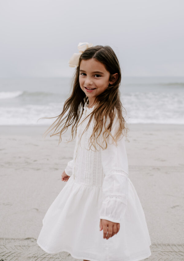 little girl in white dress twirling on beach
