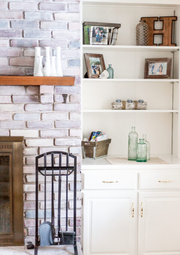 whitewash brick fireplace and white built in shelves