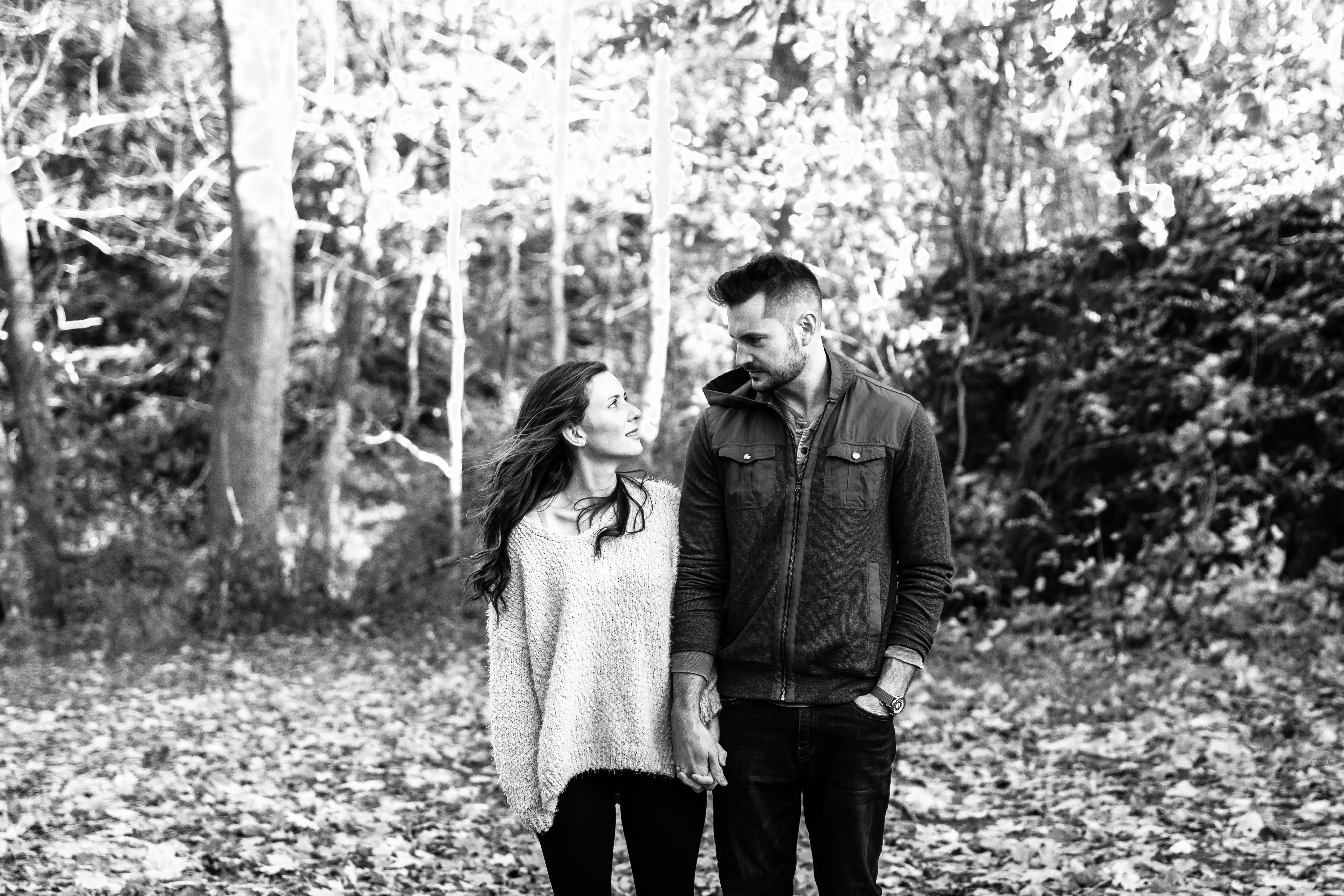 husband and wife looking at each other in forest black and white