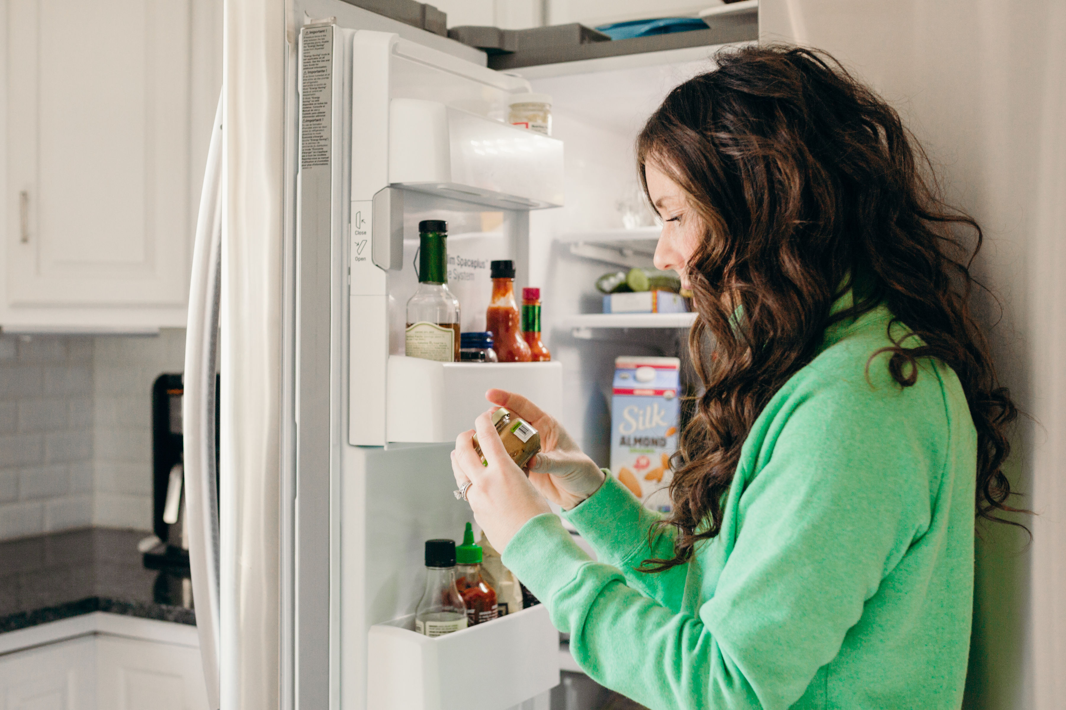 woman checking food in fridge for expiration date
