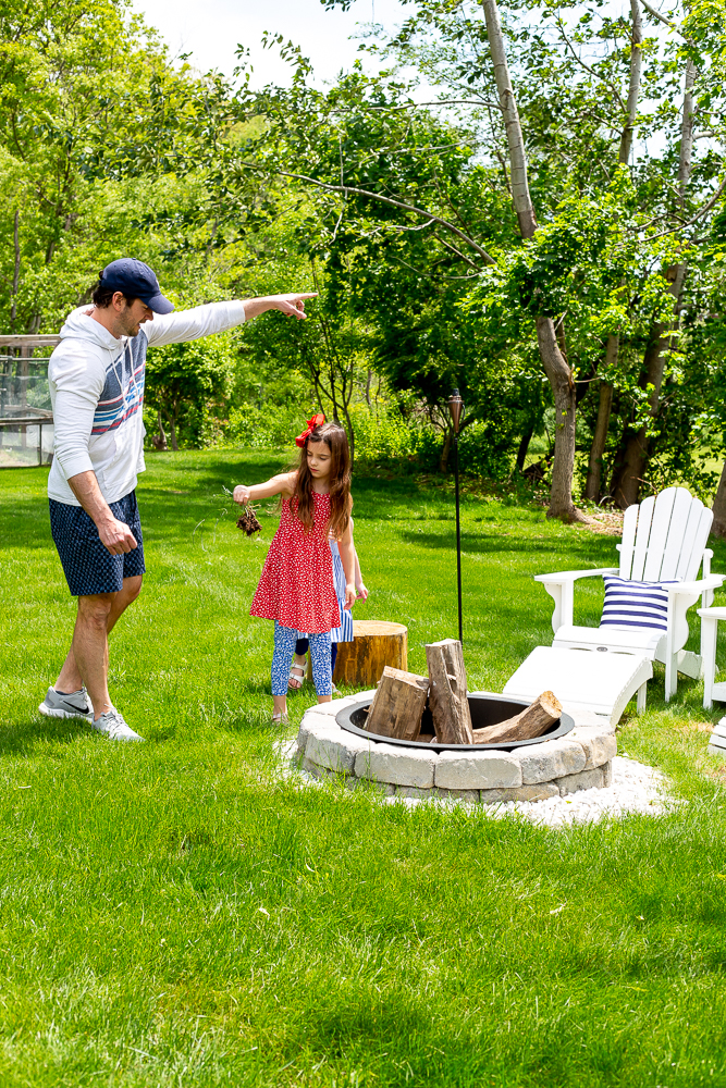 family decorating backyard and firepit area with red white and blue