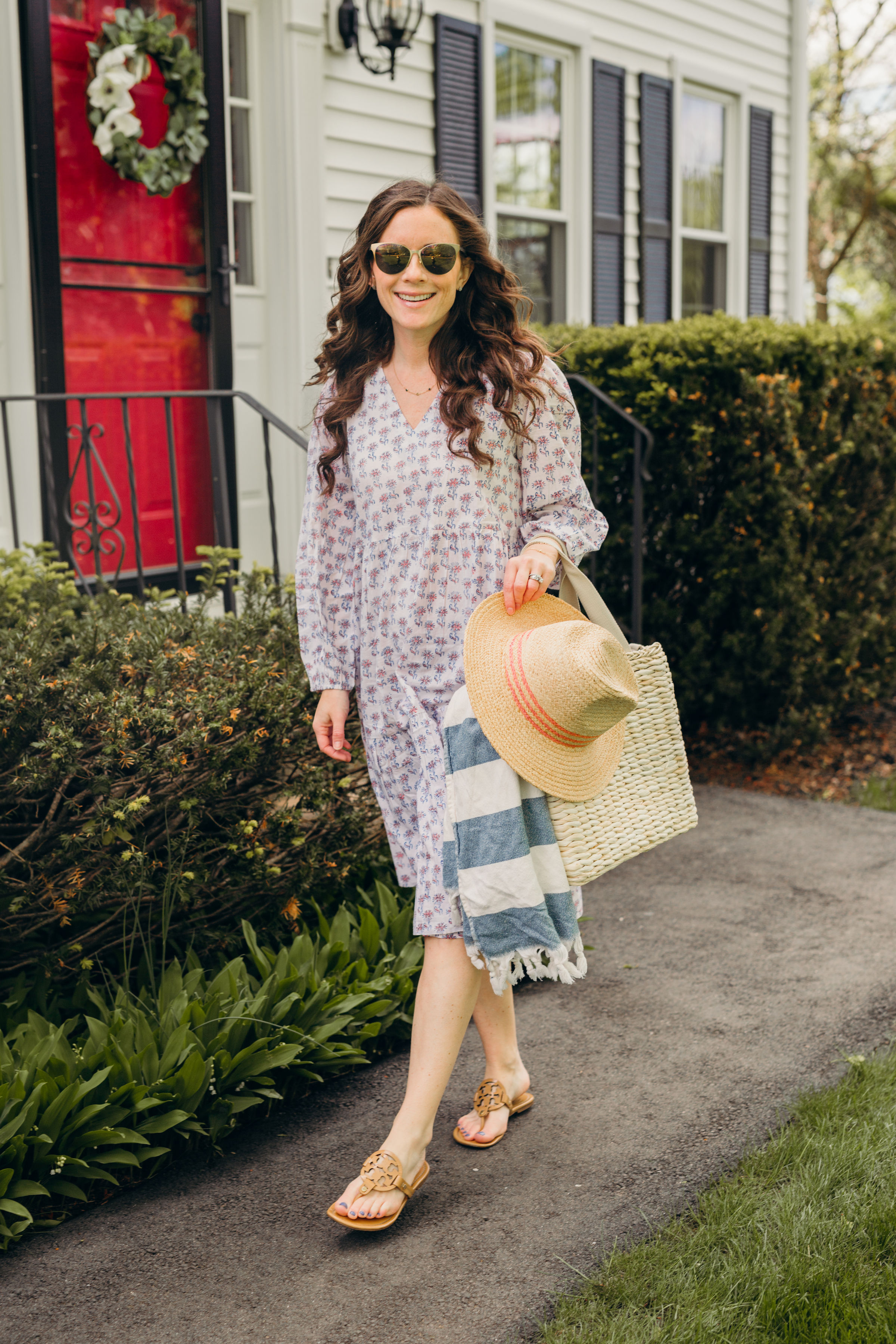 woman in swim cover up dress by shop navy bleu carrying hat and cooler tote