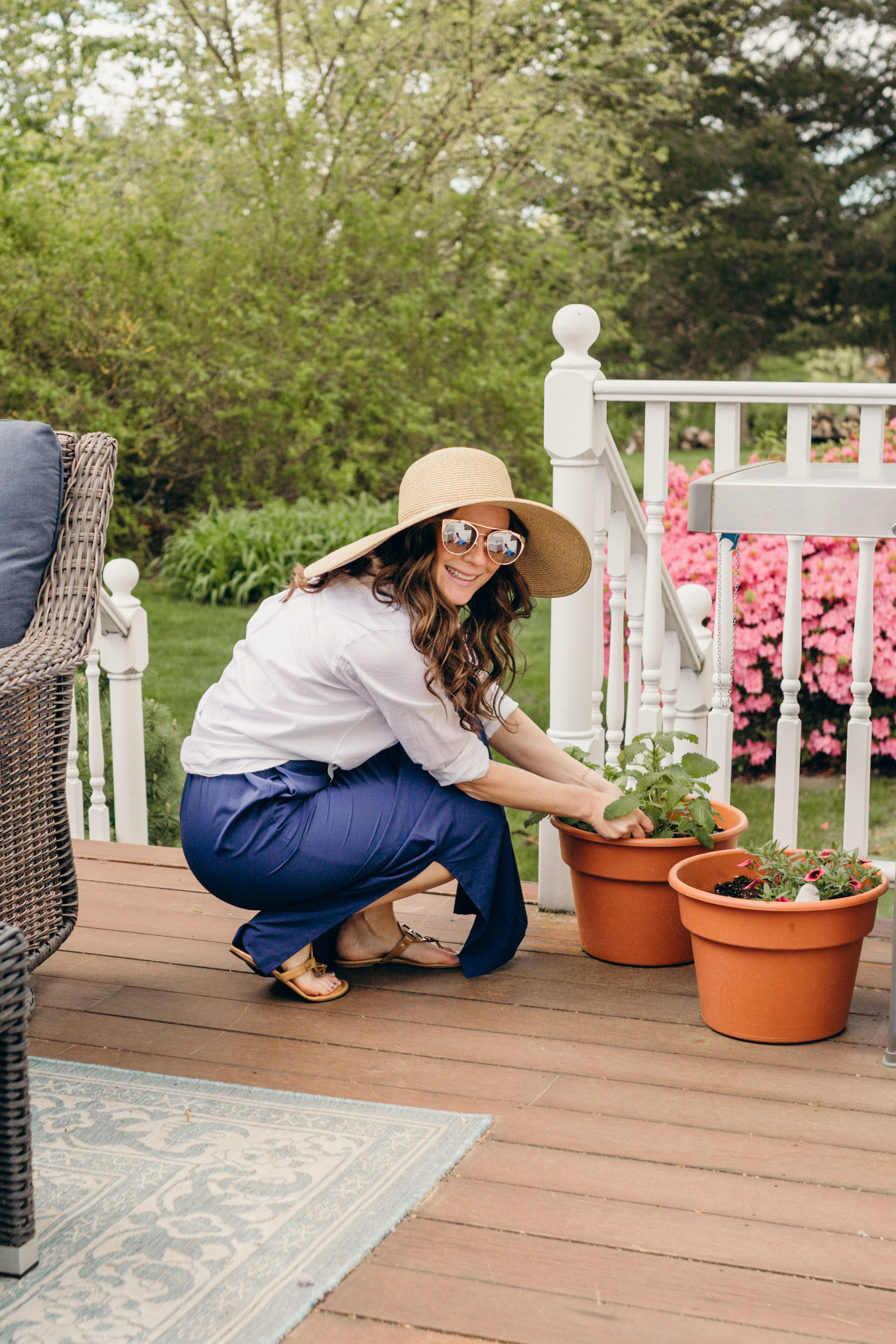 Woman planting flowers in upf clothing and sun hat