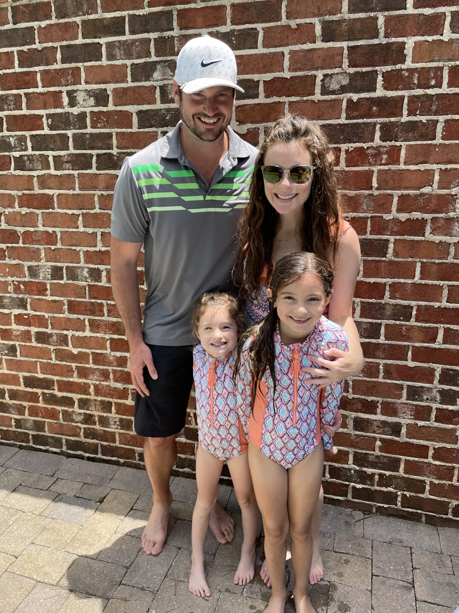 Dad in golf clothes and Mom in matching swimwear with daughters