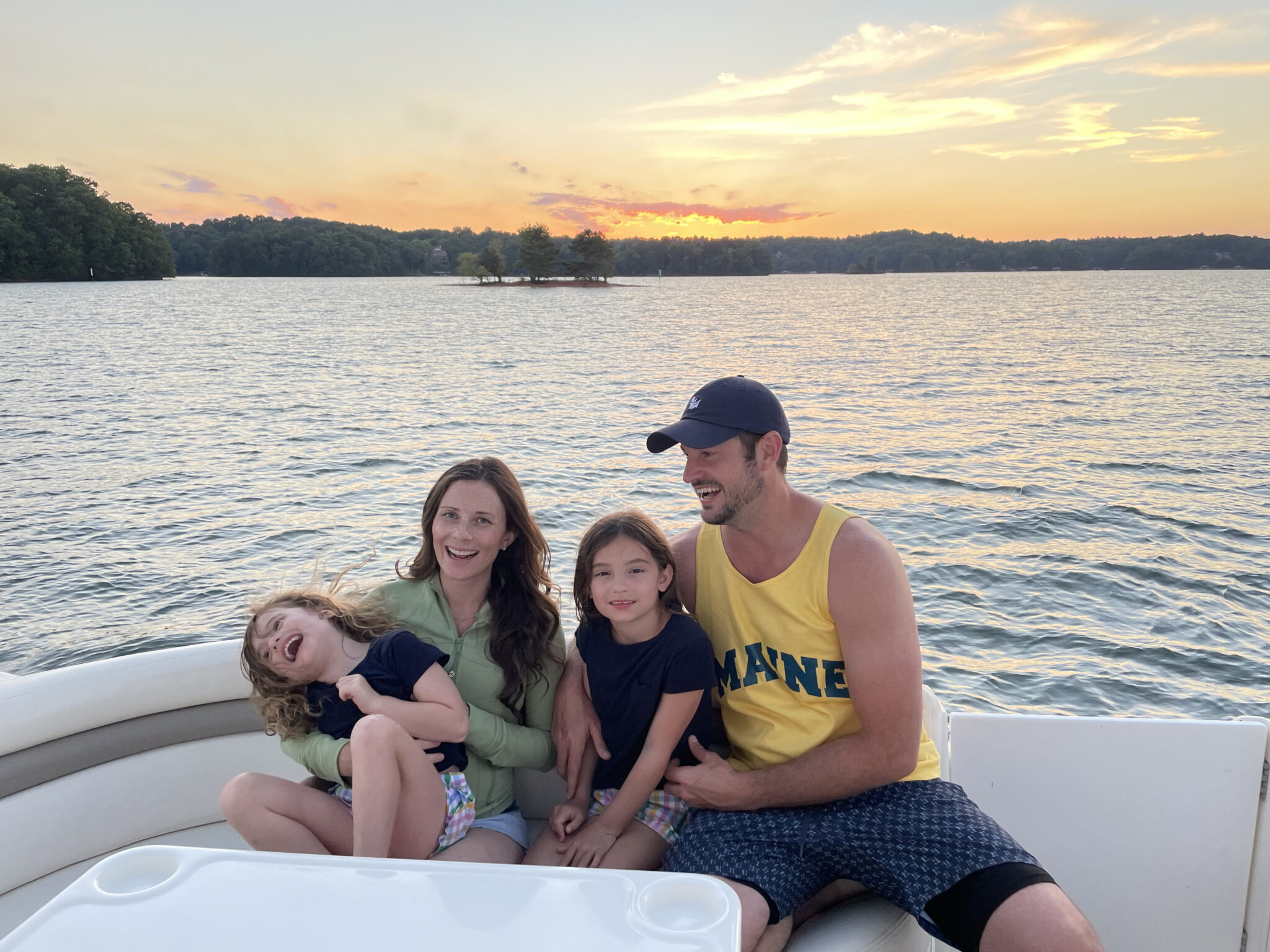 family on boat with sunrise Lake Lanier