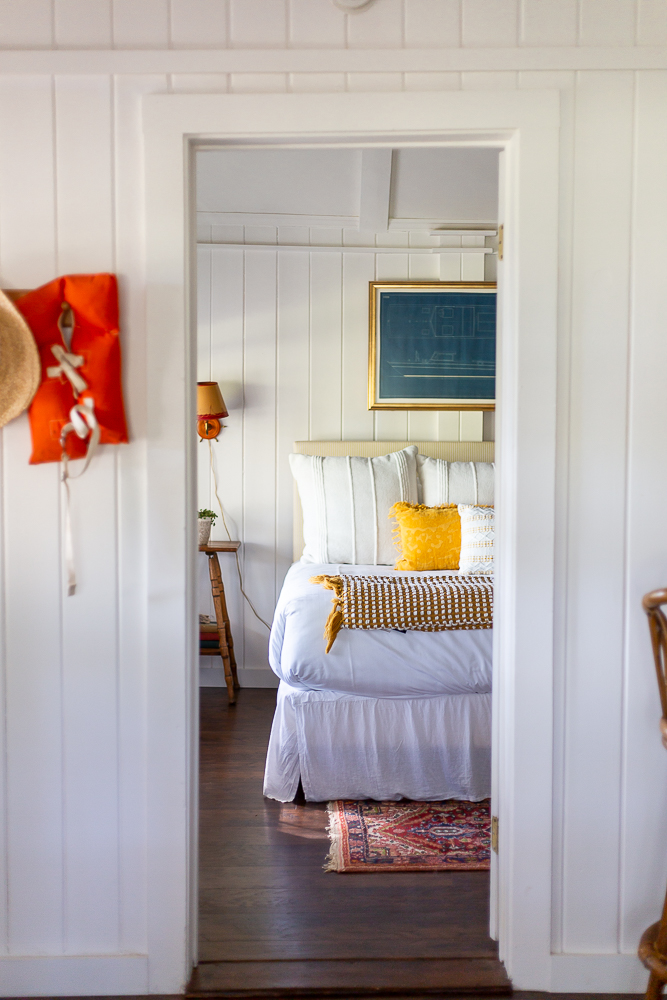 cottage bedroom with coastal Maine inspired decor yellow and red nautical accents