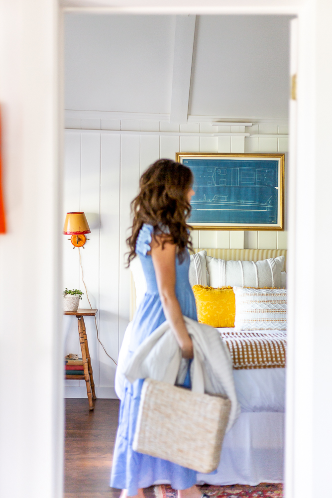 woman walking by doorway in hillhouse dress of nautical inspired cottage bedroom