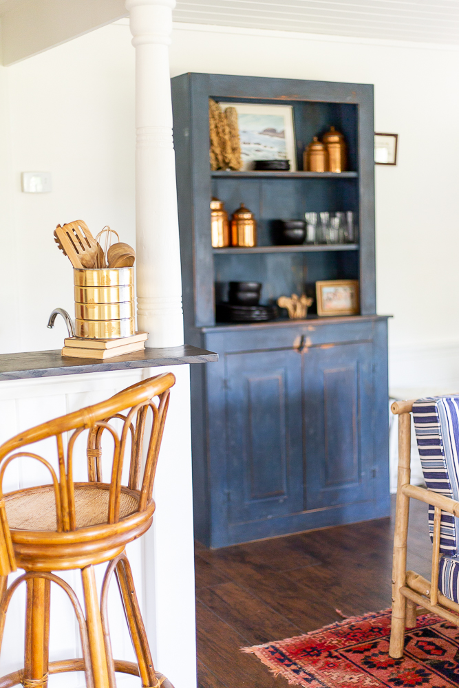 antique blue wood cabinet with coastal and bronze decor