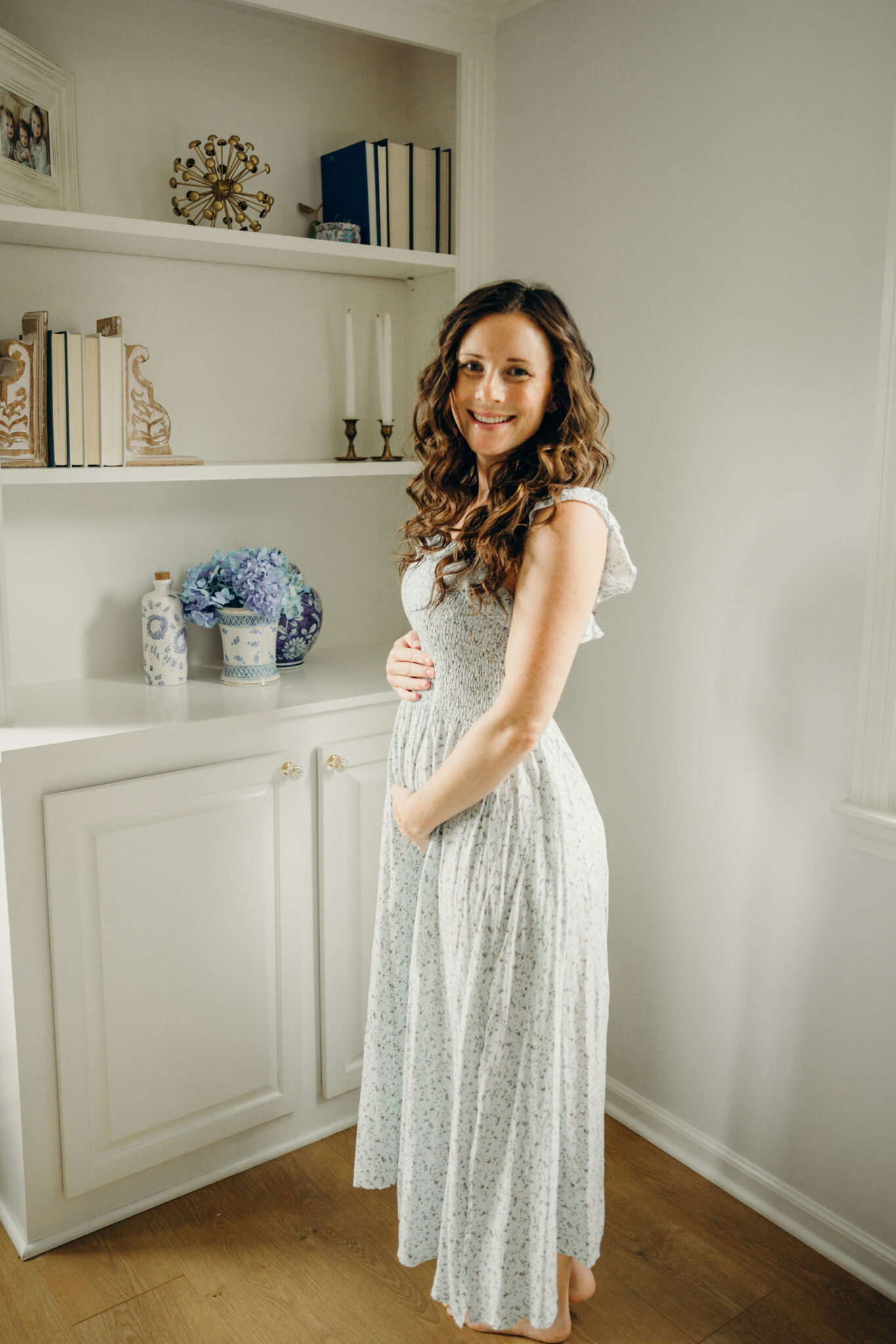 woman holding maternity bump in light blue smocked midi dress
