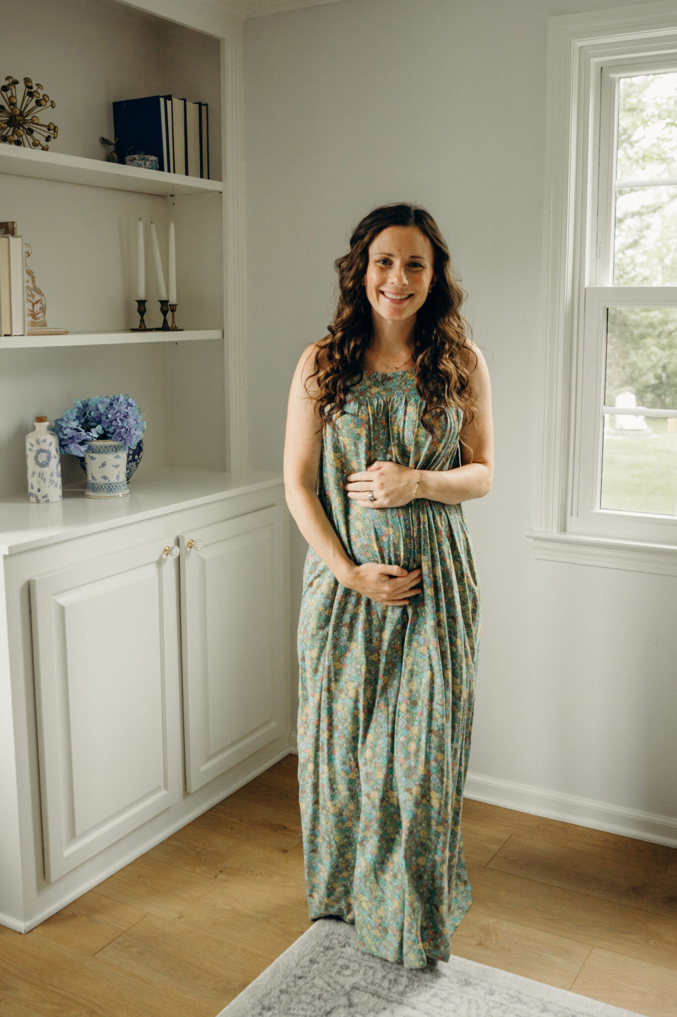 woman holding baby bump in green floral maxi dress