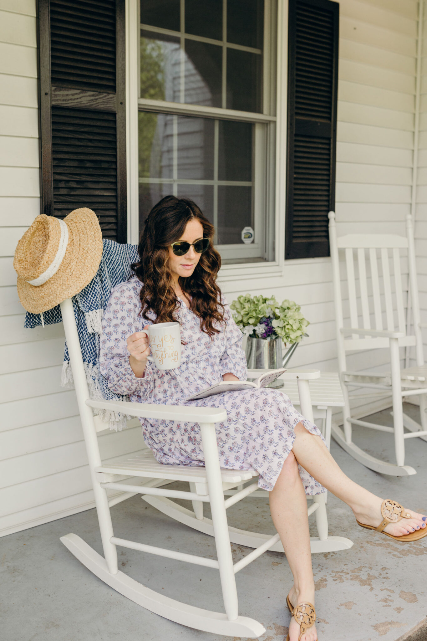 Mom with cup of coffee in rocking chair reading a book on porch